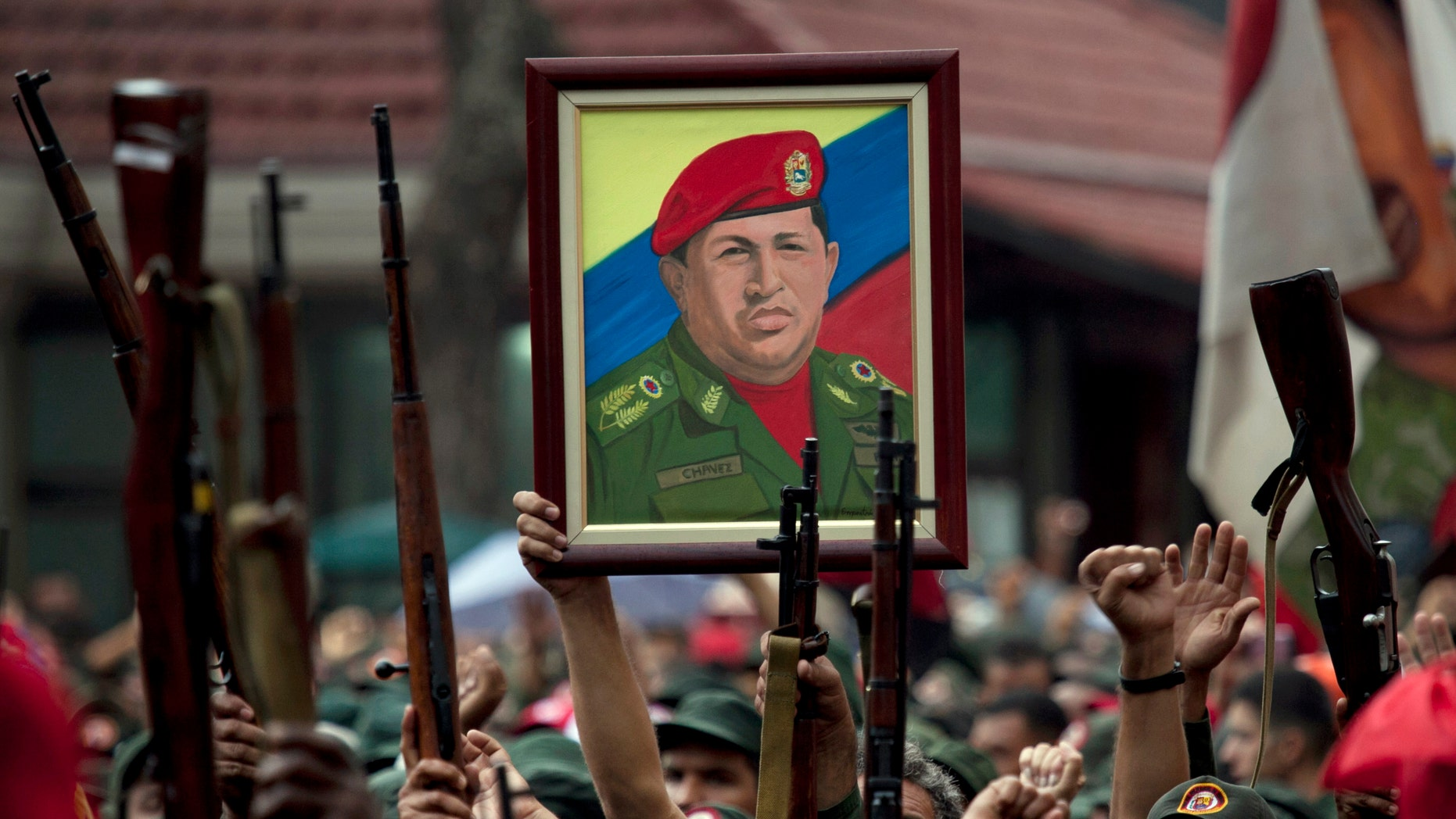 In this April 13, 2010 file photo, members of the National Revolutionary Militia hold up their weapons and a painting of Venezuela's President Hugo Chavez at an event marking the 9th anniversary of Chavez's return to power after a failed 2002 coup, in Caracas, Venezuela. (AP Photo/Ariana Cubillos, File)