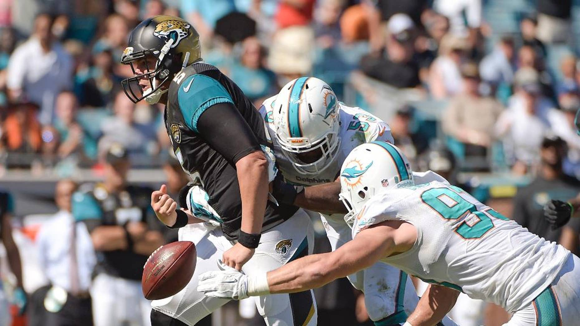 Jacksonville Jaguars quarterback Blake Bortles, left, fumbles the ball as he is hit by Miami Dolphins middle linebacker Jason Trusnik, right, and linebacker John Lotulelei, center, during the first half of an NFL football game in Jacksonville, Fla., Sunday, Oct. 26, 2014. (AP Photo/Phelan M. Ebenhack)