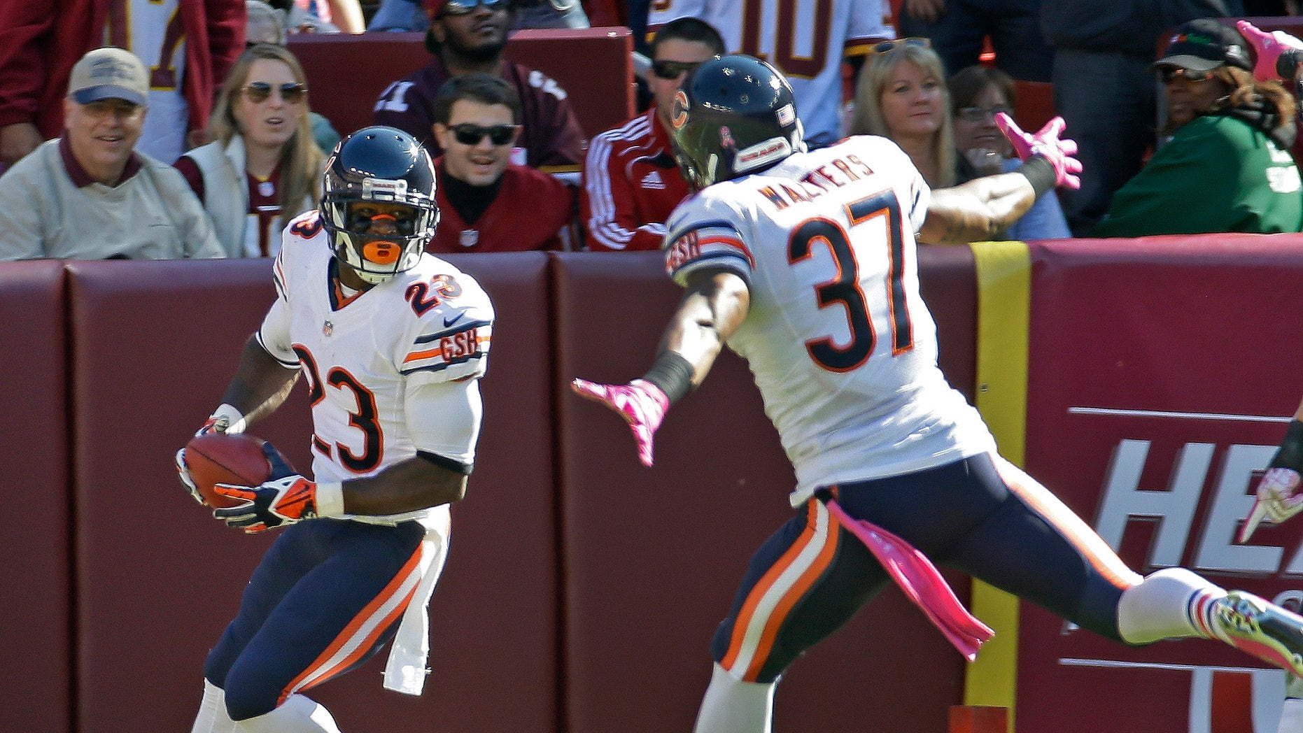 Chicago Bears wide receiver Devin Hester turns and looks at his teammate free safety Anthony Walters after scoring this 19th touchdown on a kickoff return during the first half of a NFL football game against the Washington Redskins in Landover, Md., Sunday, Oct. 20, 2013. (AP Photo/Alex Brandon)