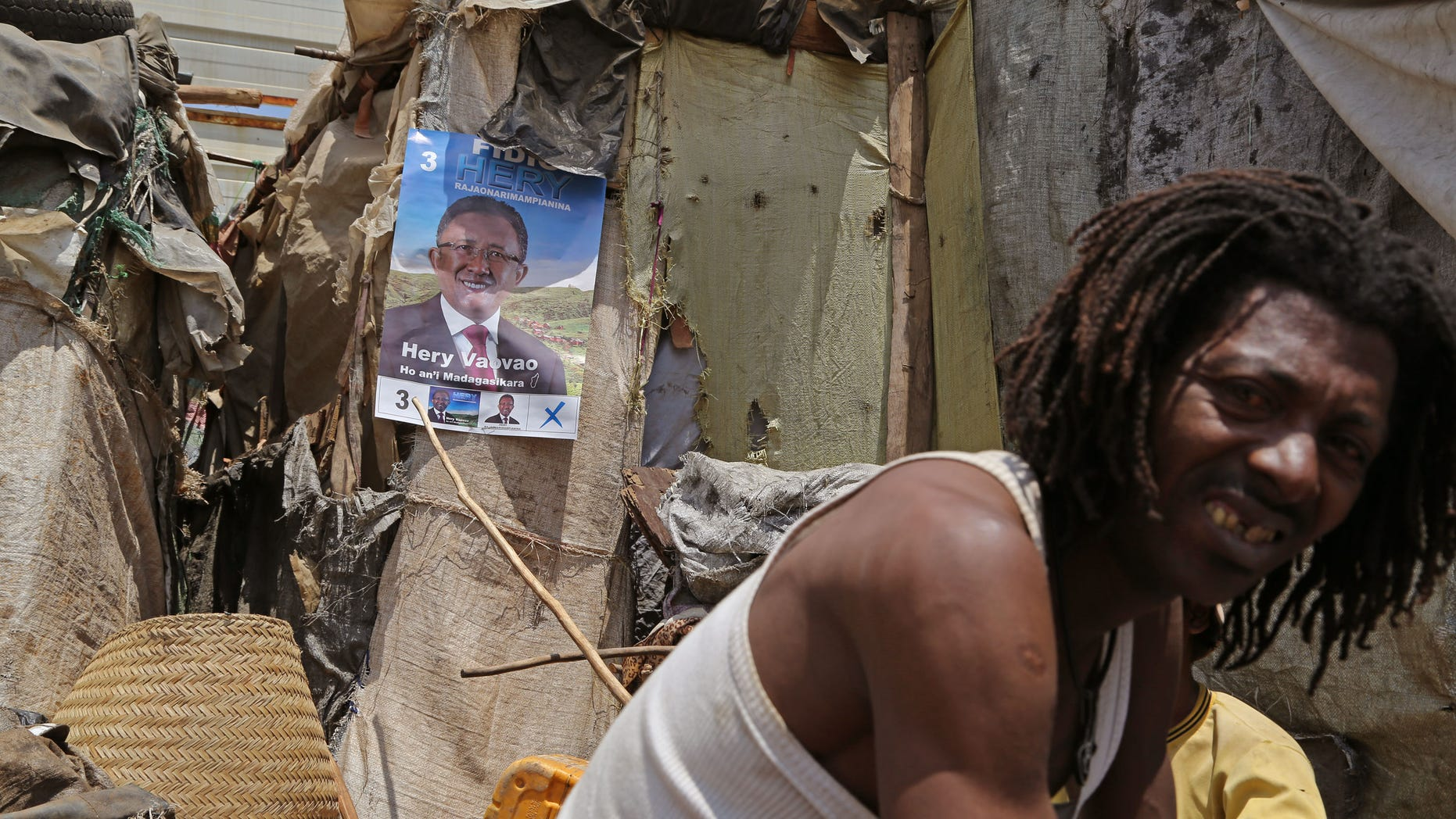A supporter of Presidential candidate Hery Rajaonarimampianina, displays his poster, outside his home in the city of Antananarivo, Madagascar, Thursday, Oct. 24, 2013.  Madagascar will hold elections on Friday that organizers hope will end political tensions that erupted in a 2009 coup and help lift the aid-dependent country out of poverty. The island nation in the Indian Ocean plunged into turmoil after Andry Rajoelina, the current president, forcibly took power from former President Marc Ravalomanana with the backing of the military.   (AP Photo/Schalk van Zuydam)