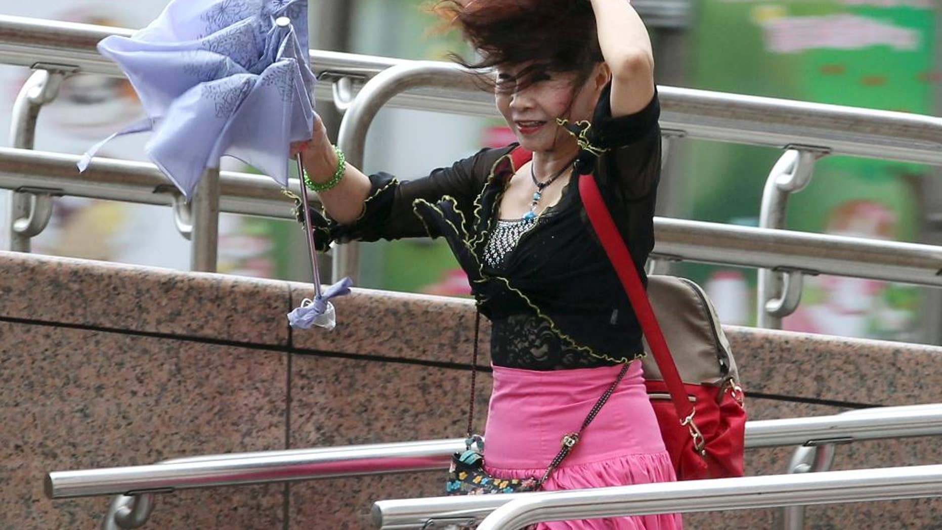 A woman struggles in the wind from Typhoon Nepartak in Taipei, Taiwan, Friday, July 8, 2016. Power was partially restored in Taiwan on Friday after Nepartak slammed into the island's eastern coast with ferocious winds and torrential rains. (Chang Hao-an/Central News Agency via AP)