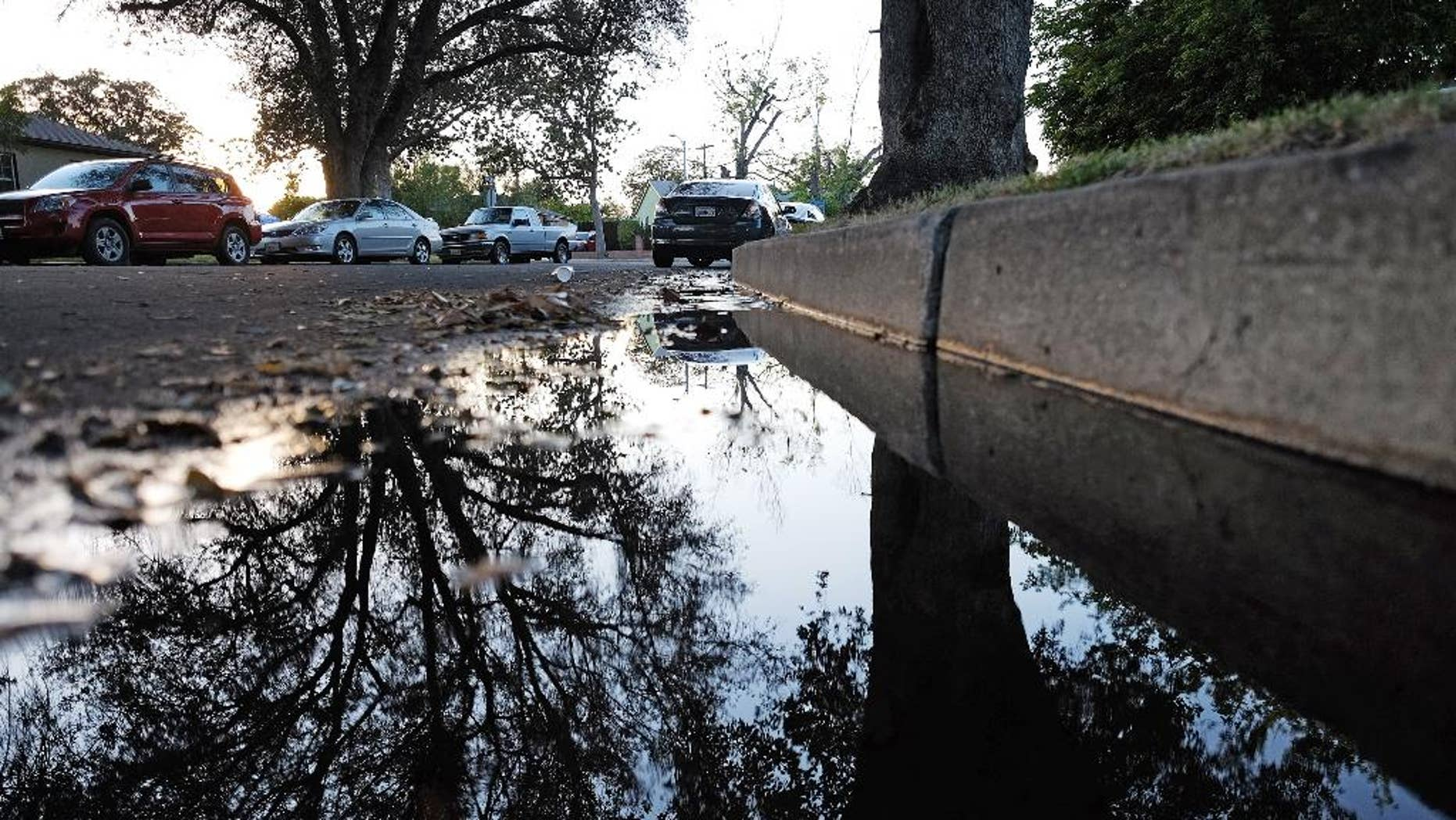 This Sunday, April 13, 2015 photo shows water from a leaking pipe flowing along the curbside of a street in Los Angeles. Southern California's water wholesaler is considering a proposal that would reduce the amount of water it delivers to more than two dozen cities and agencies in the wake of an ongoing drought. A board committee of the Metropolitan Water District meets Monday, April 13, to mull a plan to cut water deliveries by 15 percent beginning this summer.  (AP Photo/Richard Vogel)