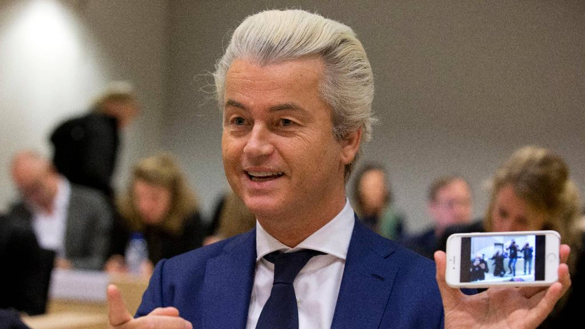 In this Friday March 18, 2016 file photo Populist anti-Islam lawmaker Geert Wilders shows a picture he took of the photographers as he appeared in court for a pretrial hearing at a high-security court on charges of inciting hatred, in Amsterdam, Netherlands. Wilders was in court Friday Sept. 23 for a pre-trial hearing in his hate speech prosecution. (AP Photo/Peter Dejong)