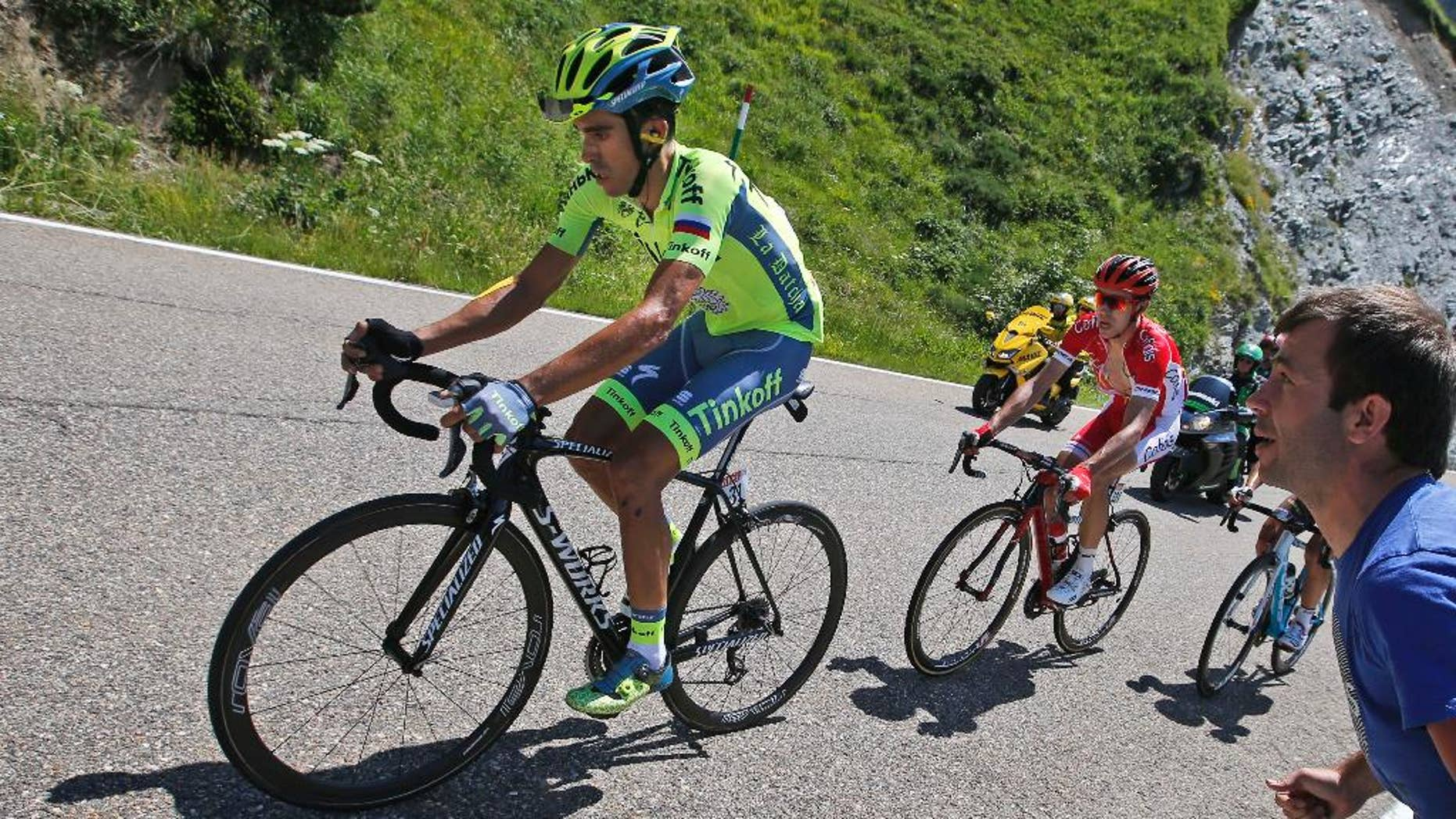 Spain's Alberto Contador, left, strains as he rides in the back of the pack with France's Nicolas Edet, right, during the ninth stage of the Tour de France cycling race Sunday.