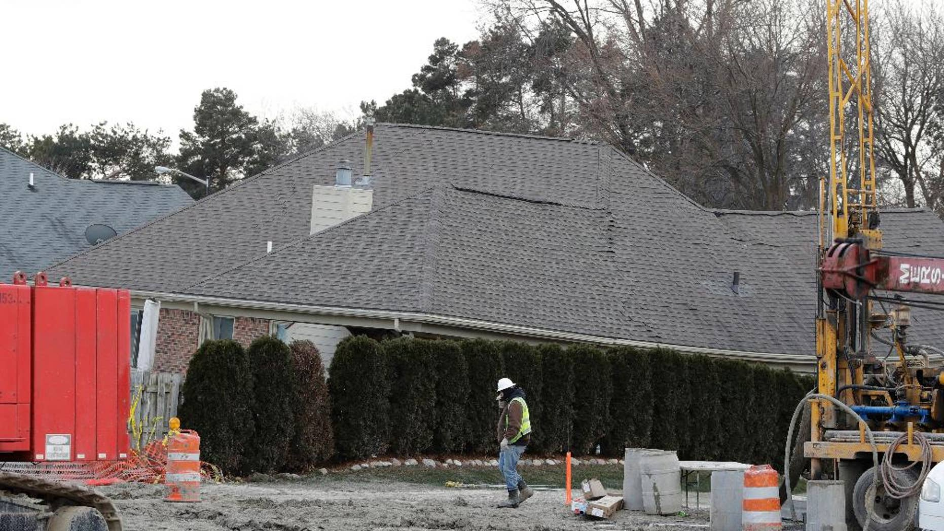 FILE - In this Wednesday, Jan. 4, 2017, file photo, a construction worker walks by a home collapsed by a sinkhole, in Fraser, Mich. Deep down inside the sinkhole's crumbled concrete and dirt is a busted sewage line that's expected to costs tens of millions of dollars and months to repair. (AP Photo/Carlos Osorio, File)