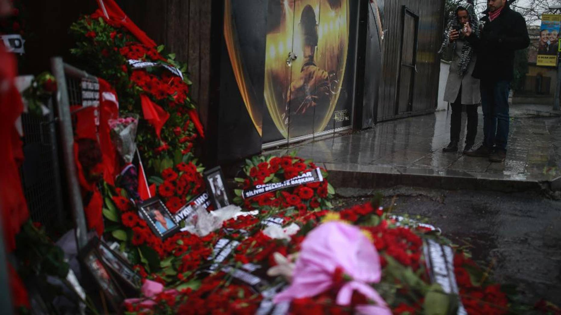 People look at floral tributes left outside the nightclub for the victims of the gunman attack, in Istanbul, Thursday, Jan. 5, 2017.  Police on Thursday conducted more raids in their hunt for the gunman that killed 39 people at an Istanbul nightclub, detaining several people at a housing complex in the city's outskirts, the state-run news agency reported. (AP Photo/Emrah Gurel)