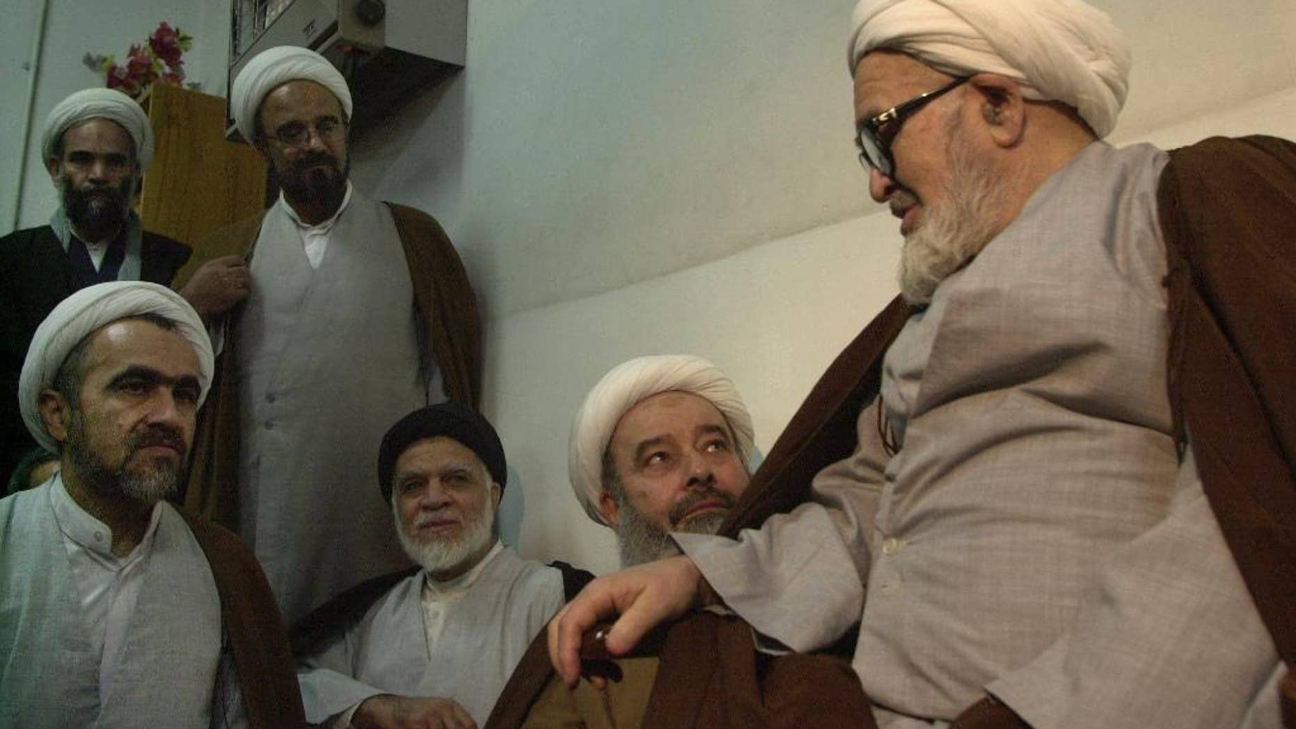 FILE -- In this Jan. 30, 2003 file photo, Grand Ayatollah Hossein Ali Montazeri, Iran's most-senior dissident cleric, right, talks to clerics and his son Ahmad, left, in Qom, 78 miles (125 kilometers) south of Tehran, Iran. Iran's semi-official Fars news agency reported Wednesday, Feb. 22, 2017 that Ahmad Montazeri, the son of late cleric Grand Ayatollah Hossein Ali Montazeri, has begun serving a six-year prison term. In November, 2016, a clerical court sentenced Ahmad Montazeri to six years in prison for publishing a tape recording of his father condemning the execution of thousands of prisoners in 1988 at the end of the country's protracted war with Iraq. (AP Photo/Vahid Salemi, File)