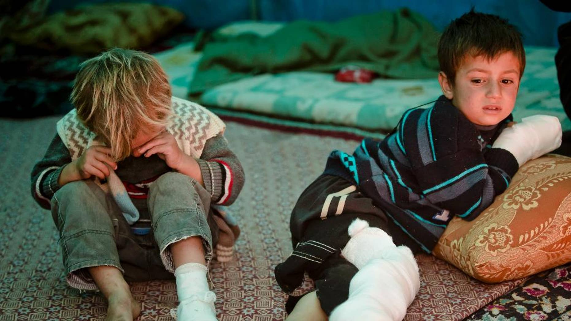 Mahmut Munir, 8 years-old, right, a Syrian Kurdish refugee boy from Kobani and his 5 year-old brother Mahmut, left, who were injured along with other family members in a mortar attack by forces of the Islamic State group sits in a tent at a camp in Suruc, on the Turkey-Syria border Wednesday, Nov. 19, 2014. Kobani, also known as Ayn Arab, and its surrounding areas, has been under assault by extremists of the Islamic State group since mid-September and is being defended by Kurdish fighters. (AP Photo/Vadim Ghirda)