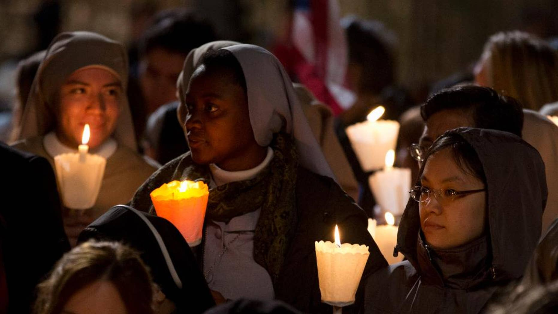 Faithful attend the Via Crucis (Way of the Cross) torchlight procession celebrated by Pope Francis in front of the Colosseum on Good Friday in Rome, Friday, April 18, 2014. (AP Photo/Gregorio Borgia)