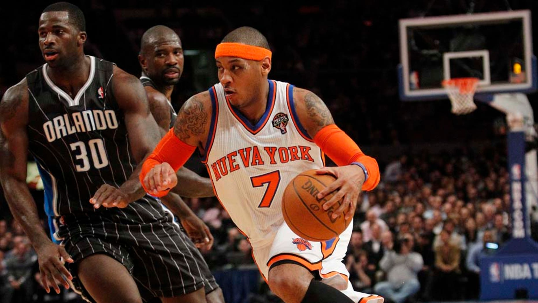 New York Knicks' Carmelo Anthony drives past Orlando Magic's Brandon Bass during the first half of an NBA basketball game on Wednesday, March 23, 2011, in New York. (AP Photo/Frank Franklin II)