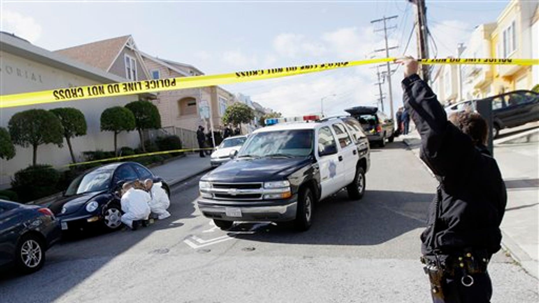 March 23: San Francisco Police officers inspect outside of a home on Howth Street in San Francisco.