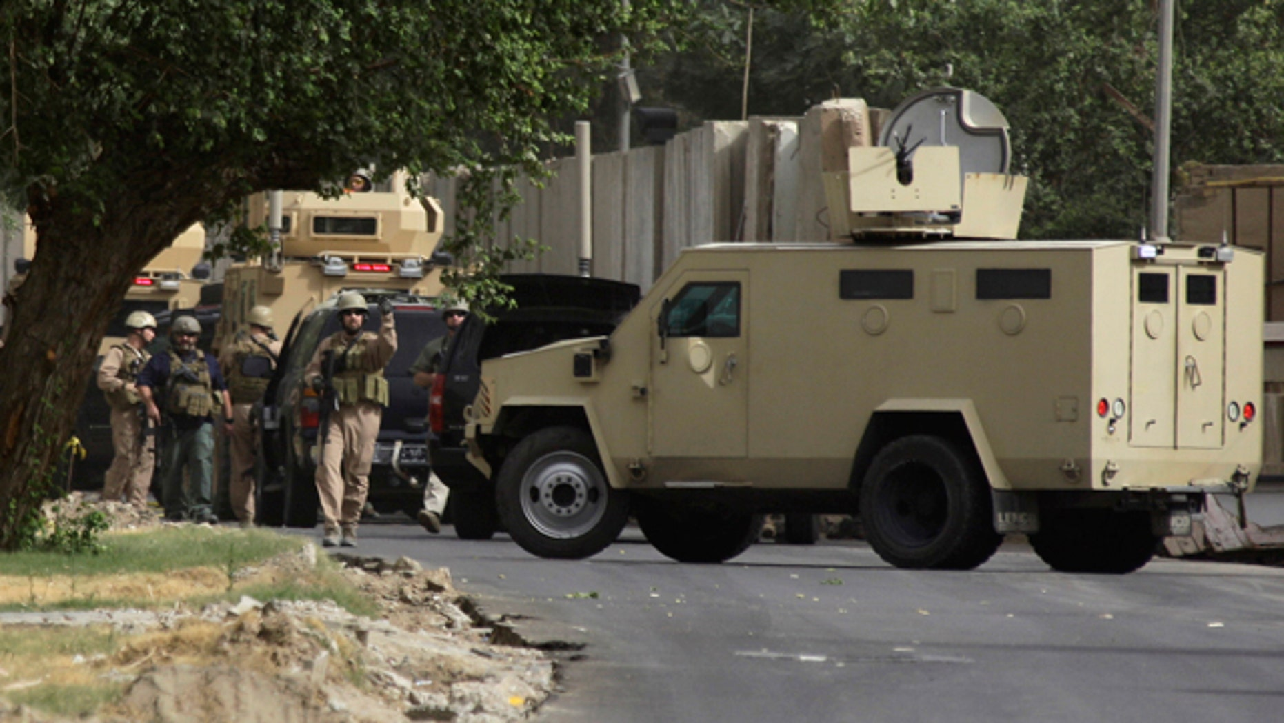 June 6: Security contractors inspect their armored vehicles after a roadside bomb attack in Baghdad, Iraq.