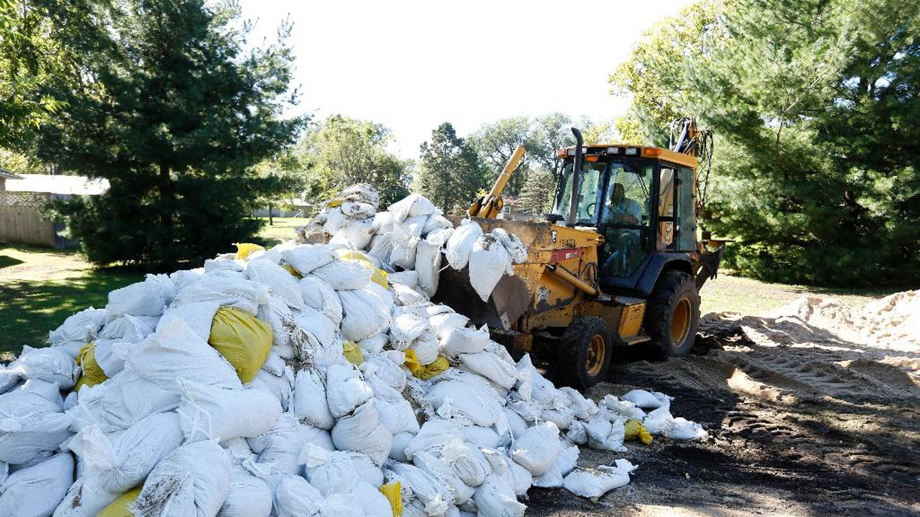 A Waterloo City worker removes sandbags piled up on Belle Street after the Cedar River receded from homes in the area Monday, Sept. 26, 2016, in Cedar Falls, Iowa. (Matthew Putney/The Waterloo Courier via AP)