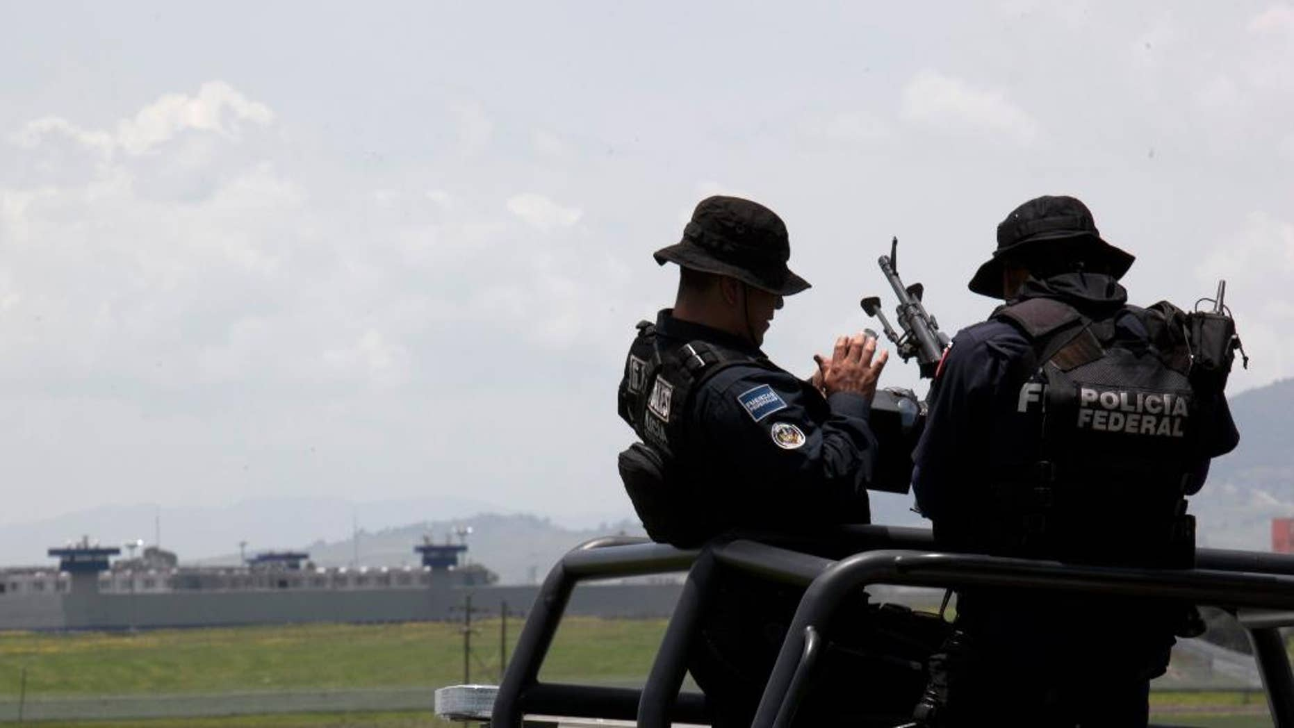 "Federal Police man their weapons aboard a pick up truck, near the half-built house where drug lord Joaquin ""El Chapo"" Guzman made his escape through a tunnel from the Altiplano maximum security prison in Almoloya, west of Mexico City, Monday, July 13, 2015. The Altiplano prison can be seen in the background. A widespread manhunt that included highway checkpoints, stepped up border security and closure of an international airport failed to turn up any trace of ""El Chapo"" Guzman by Monday, more than 24 hours after he escaped through an underground tunnel in his cell. (AP Photo/Marco Ugarte)"