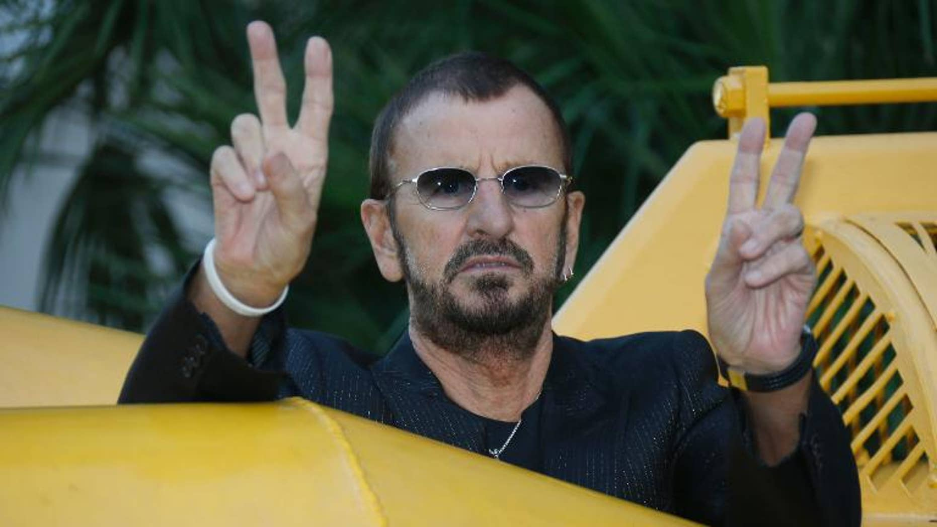 """British artist and former drummer for the Beatles Ringo Starr poses next to a 1964 yellow submarine before the """"Passion Ocean"""" exhibition inauguration on September 24, 2013 in Monaco."""