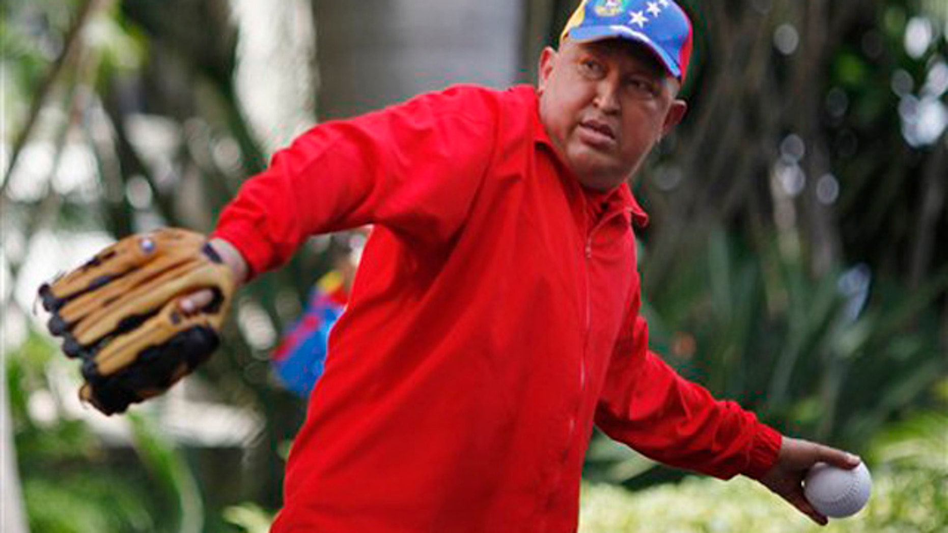 In this photo released by Miraflores Press Office, Venezuela's President Hugo Chavez throws a softball after giving a live address on state TV at Miraflores presidential palace in Caracas, Venezuela, Thursday Sept. 29, 2011.