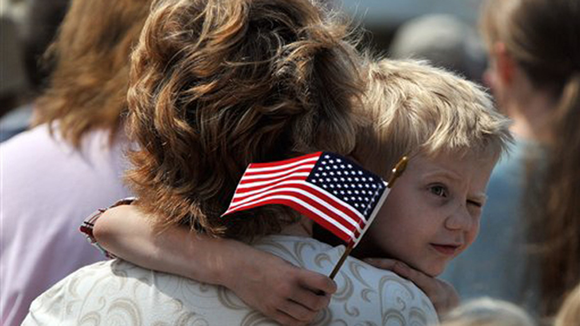 FILE -- Monday, May 28, 2012: Austin Bunyard, 5, squints in the bright sun as he watches veterans salute the American flag during a Memorial Day ceremony on the Rock Island Arsenal in Rock Island, Ill.