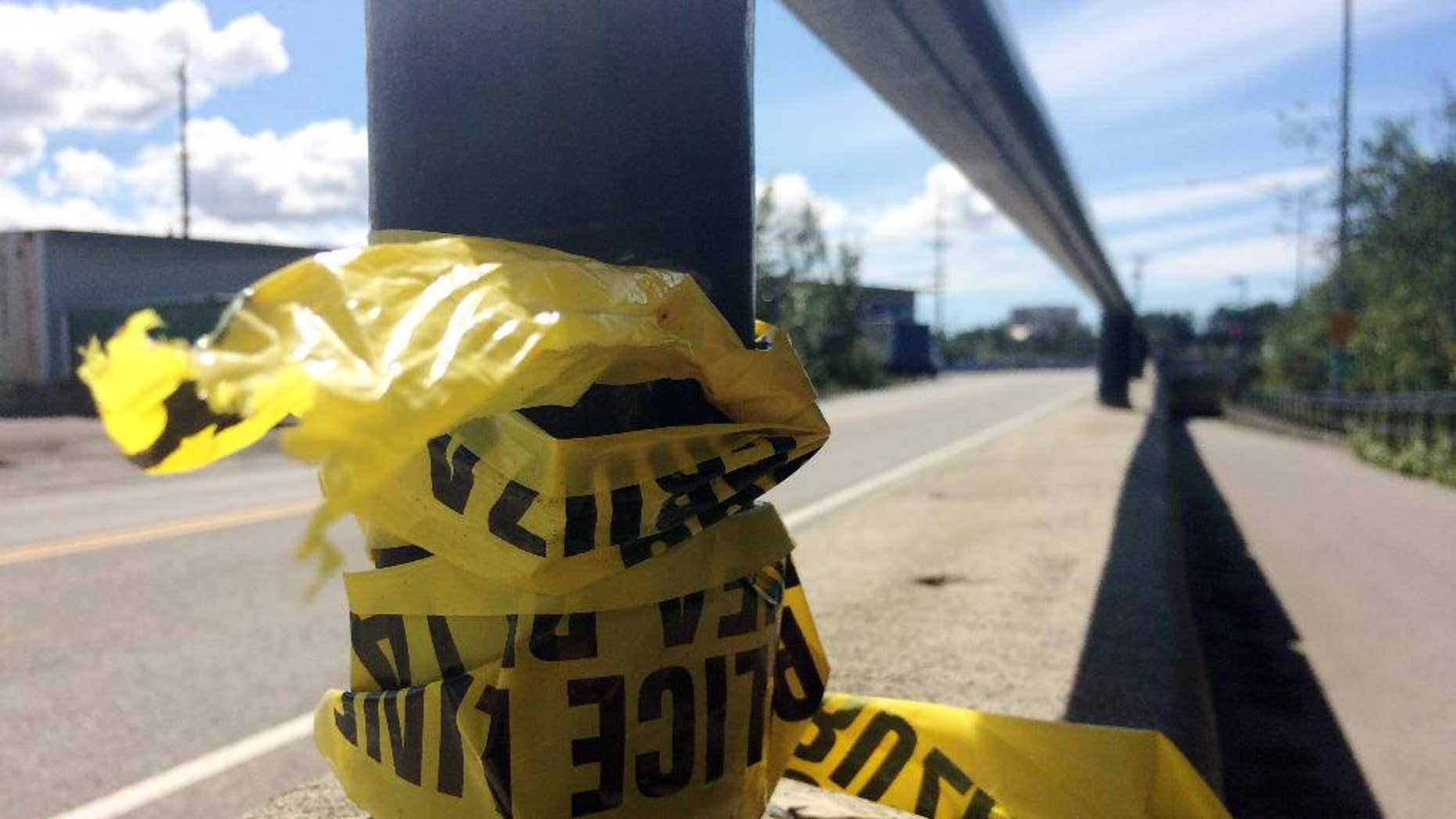 Police tape hangs from a hand rail near where two people were killed on the Ship Creek Trail in downtown Anchorage, Alaska, in July.