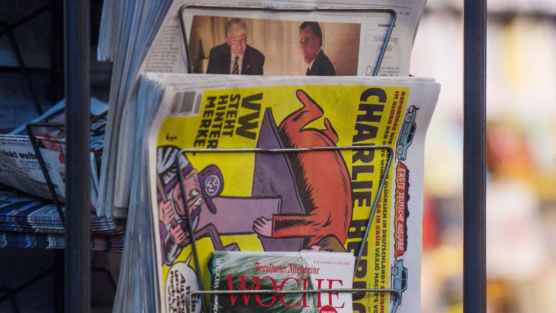 Copies of the French satirical magazine Charlie Hebdo sit at a newsagent's in Stuttgart, Germany, Thursday, Dec. 1, 2016.  The first German edition went on sale on Thursday morning. (Lino Mirgeler/dpa via AP)