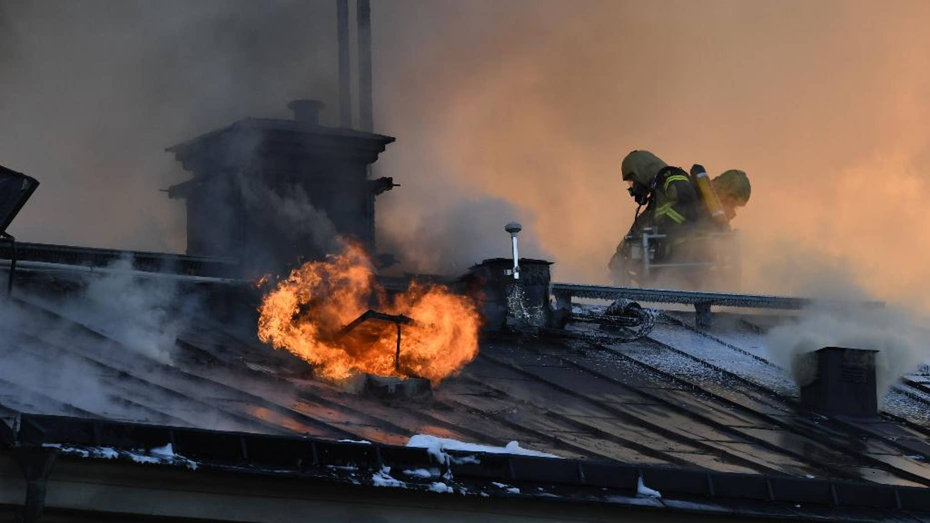 Firefighters try to extinguishing a fire at the Royal Institute of Art in Stockholm, Sweden, Wednesday, Sept. 21, 2016. A fire has started in a building belonging to Stockholm's Royal Institute of Art, sending a plume of smoke over large parts of the Swedish capital. Dozens of firefighters struggled to contain the blaze, which raced through the attic and roof of the building on Skeppsholmen island near downtown Stockholm on Wednesday. There were no reports of injuries. (Anders Wiklund/TT News Agency via AP)