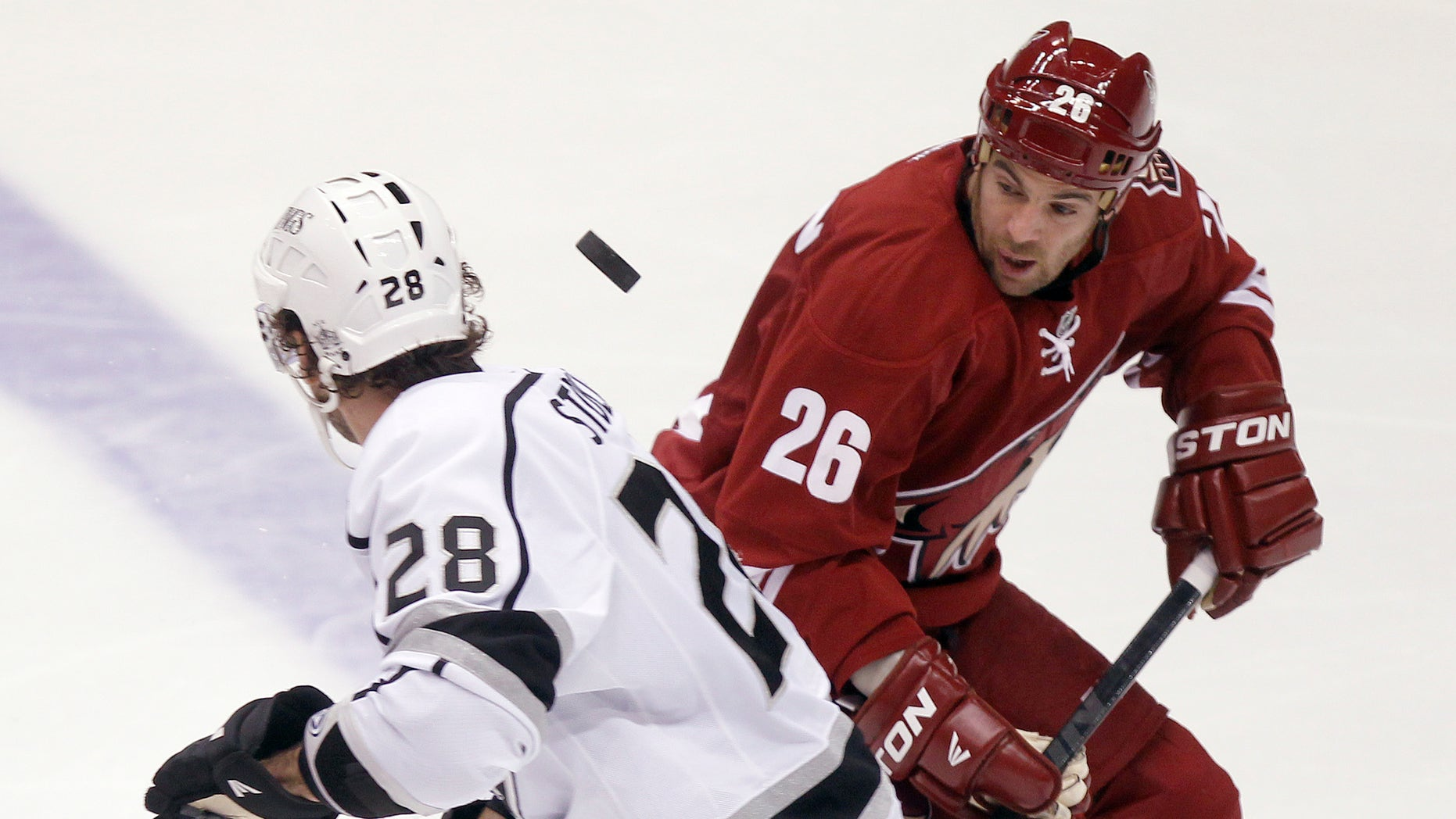 Los Angeles Kings center Jarret Stoll, left, and Phoenix Coyotes left winger Steve Sullivan, right, looks to gain control of a loose puck in the third period of an NHL hockey game Tuesday, April 2, 2013, in Glendale, Ariz. The Coyotes won 3-1. (AP Photo/Paul Connors)
