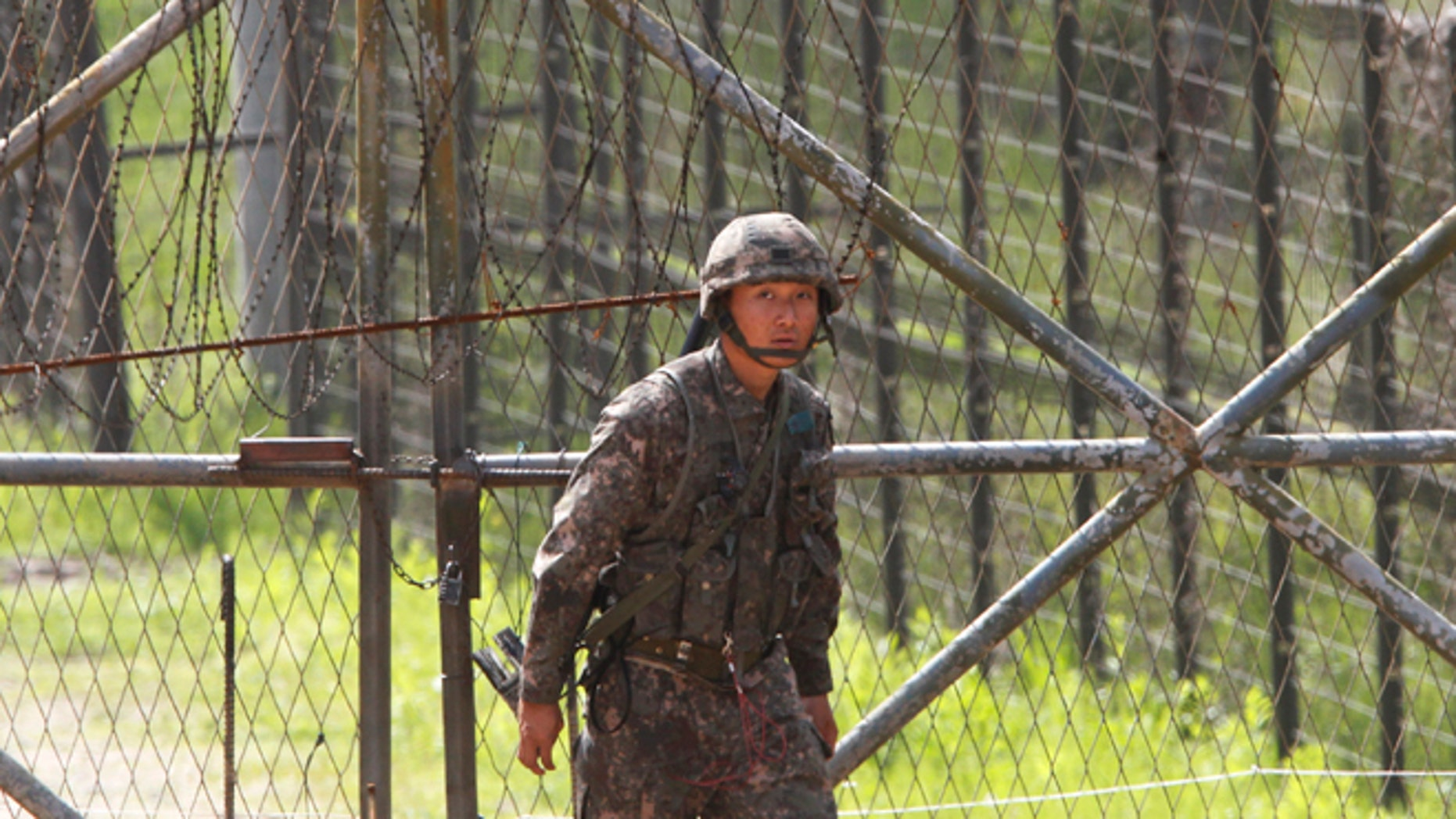 May 19, 2013: A South Korean army soldier passes by a barbed-wire fence in Paju, South Korea, near the border village of Panmunjom.