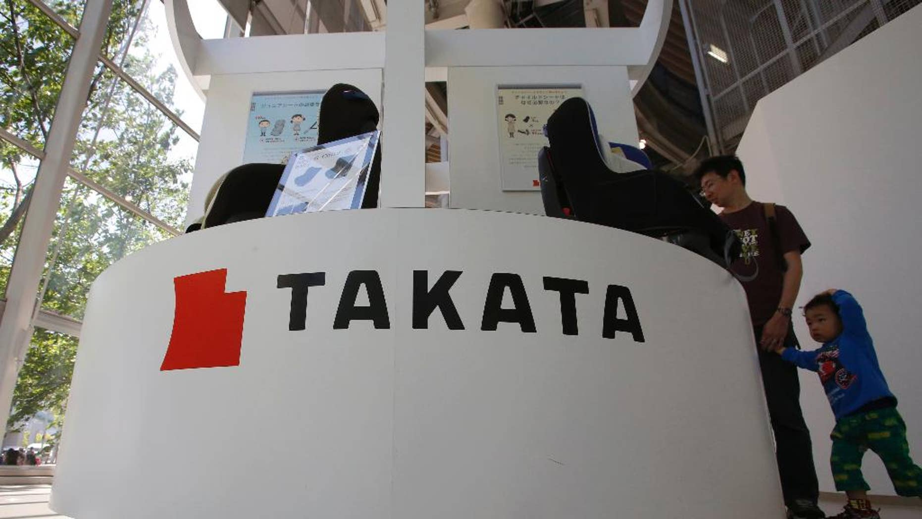 In this Wednesday, May 4, 2016 photo, visitors look at child seats manufactured by Takata Corp. at an automaker's showroom in Tokyo. Takata, the Japanese auto-parts maker behind a massive air-bag recall, is expecting a return to profit for the fiscal year through March 2017, although it just agreed to do more recalls. Tokyo-based Takata reported a 13 billion yen ($120 million) loss Wednesday, May 11, for the fiscal year ended March — the second straight year of red ink. (AP Photo/Shizuo Kambayashi)
