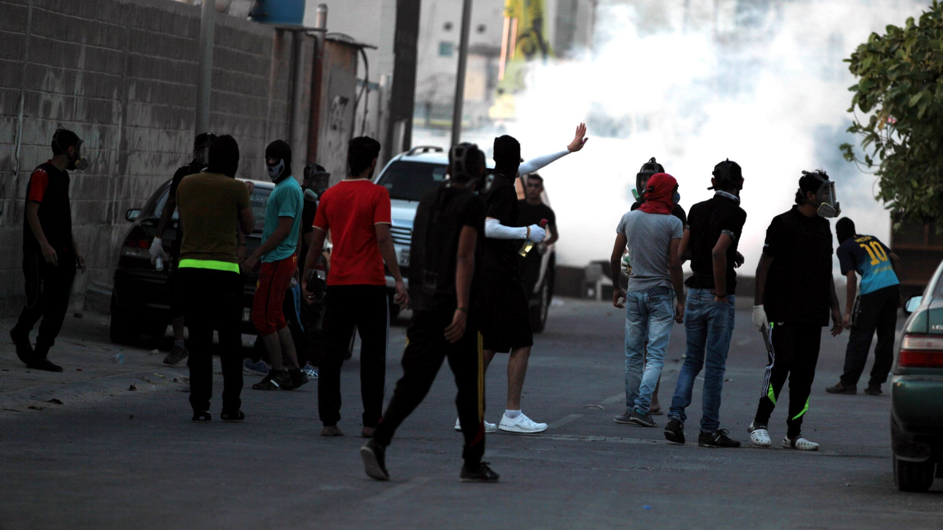 Bahraini youths carrying petrol bombs and stones confront riot police firing tear gas, stun grenades and shotguns after the funeral for Hussain Mahdi Habib, 20, in Sitra, Bahrain, on Sunday, Oct. 20, 2013. Habib, who was wanted by authorities for escaping from prison, received  a 15-year sentence in absentia for his participation in the pro-democracy uprising, and was found beaten and shot dead. (AP Photo/Hasan Jamali)