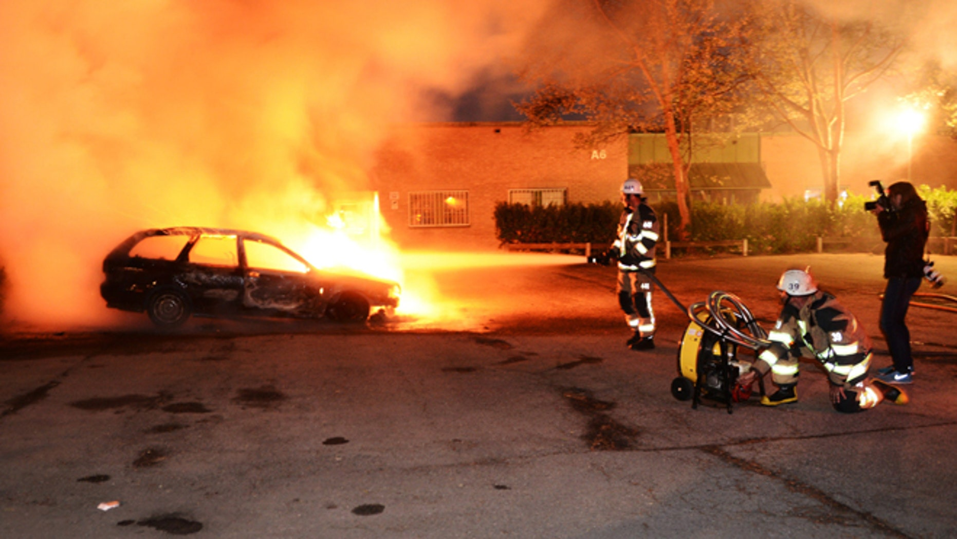 May 21, 2013: Firemen extinguish a burning car in the Stockholm suburb of Kista after youths rioted in several different suburbs around Stockholm for a third consecutive night.