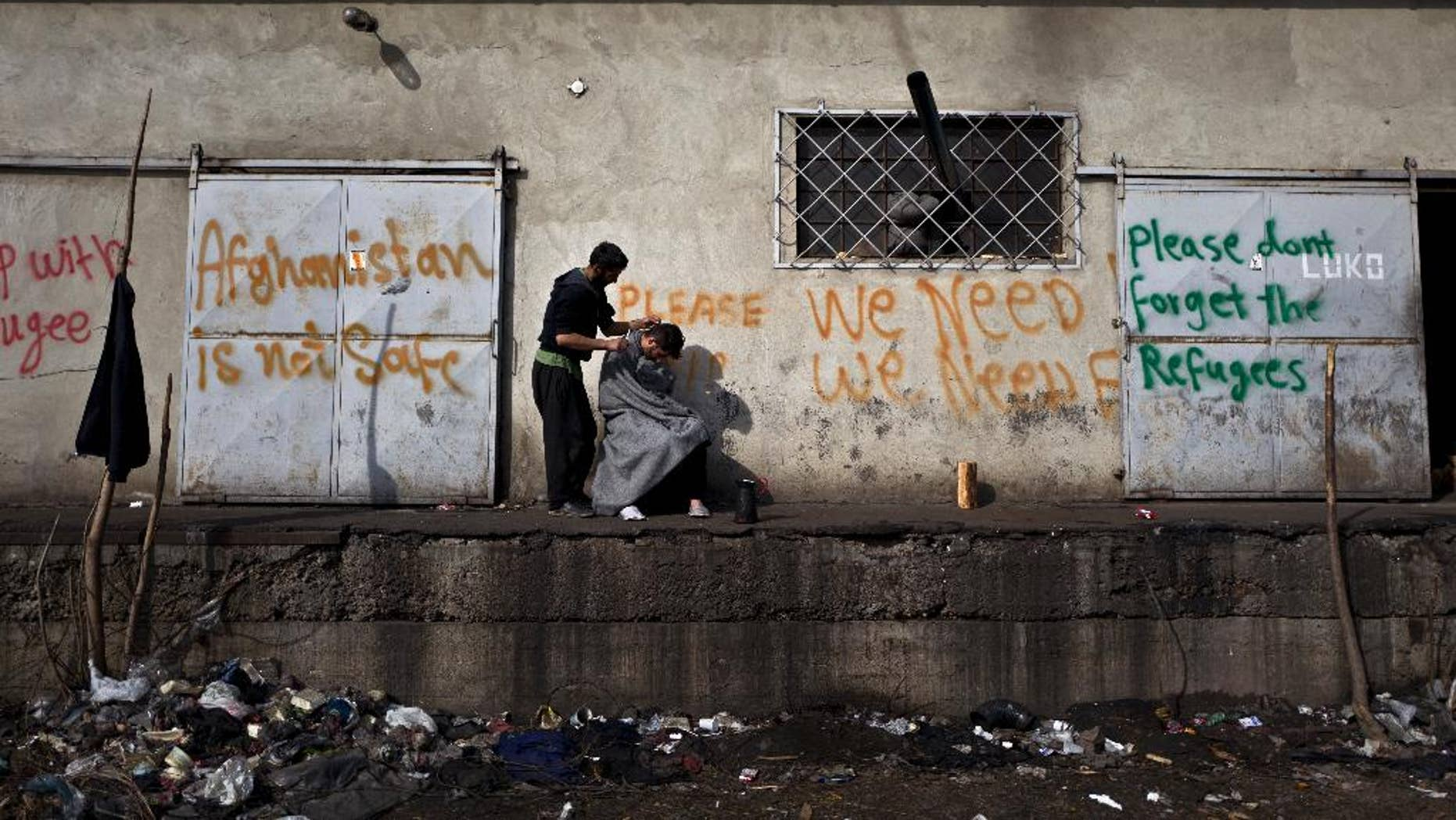 An Afghan refugee man gives a haircut to a friend in an abandoned warehouse where they have taken refuge in Belgrade, Serbia, Wednesday, Feb. 22, 2017. Hundreds of migrants have been sleeping rough in freezing conditions in central Belgrade looking for ways to cross the heavily guarded EU borders. (AP Photo/Muhammed Muheisen)