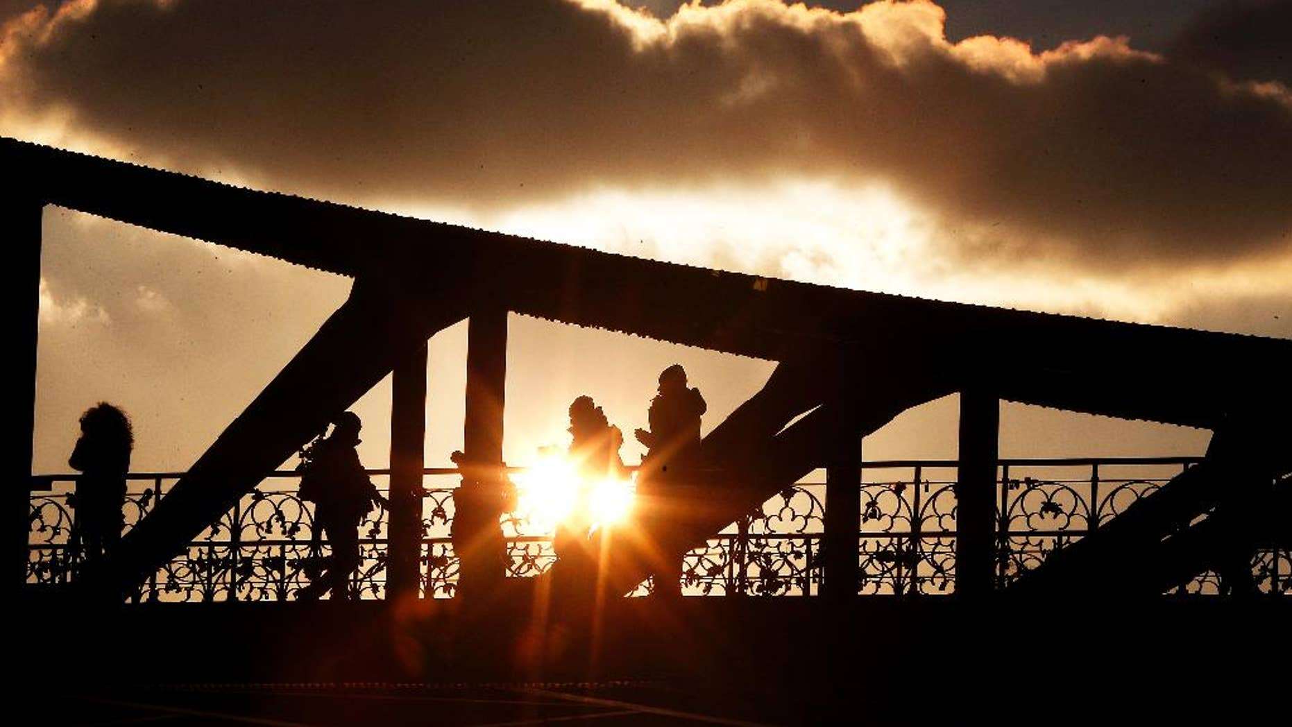 People walk over a pedestrian bridge over the river Main as the sun sets in Frankfurt, central Germany, Monday, Jan. 16, 2017. (AP Photo/Michael Probst)
