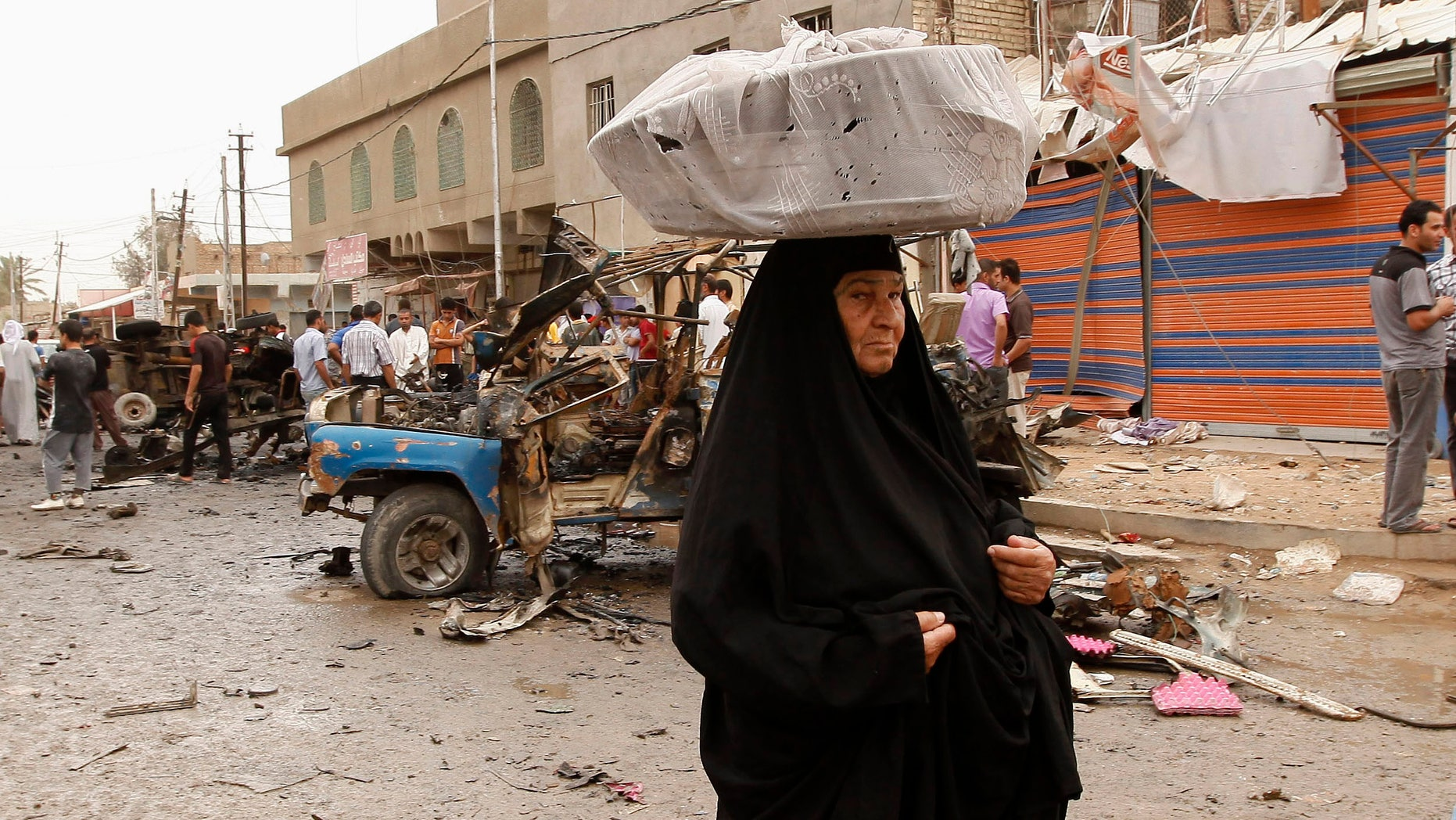 An Iraqi woman, who sells milk, passes by the scene of a car bomb attack in the Kamaliyah neighborhood, a predominantly Shiite area of eastern Baghdad, Iraq, Monday, May 20, 2013. A wave of car bombings across Baghdad's Shiite neighborhoods and in the southern city of Basra killed and wounded scores of people, police said. (AP Photo/ Hadi Mizban)