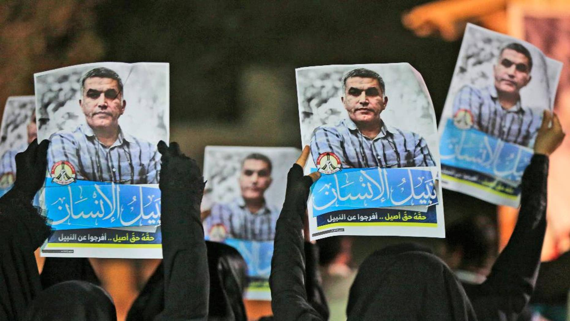"""FILE- In this Thursday, May 14, 2015 file photo, Bahraini anti-government protesters hold up images of jailed human rights activist Nabeel Rajab during a solidarity protest outside his home in Bani Jamra, Bahrain. A jailed activist in Bahrain on trial for allegedly spreading """"false news"""" is being investigated over a letter published in his name by French newspaper. Bahrain's Interior Ministry issued a statement early Thursday, Dec. 22, 2016,  announcing the new probe focusing on Nabeel Rajab over the article published by Le Monde on Tuesday. (AP Photo/Hasan Jamali, File)"""