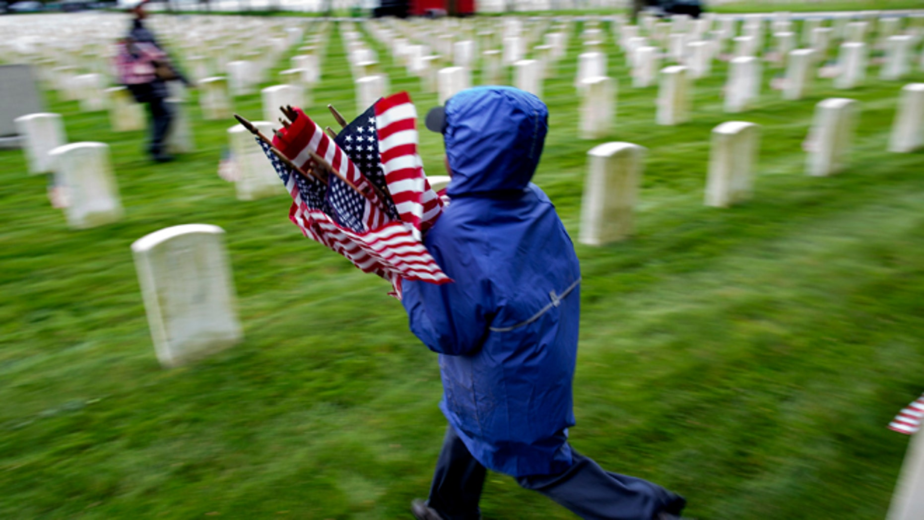 Jabari Nedd, 9, of New York, eagerly carries American Flags he and other volunteers were placing on graves at Cypress Hills National Cemetery in the Brooklyn borough of New York, Saturday, May 25, 2013.