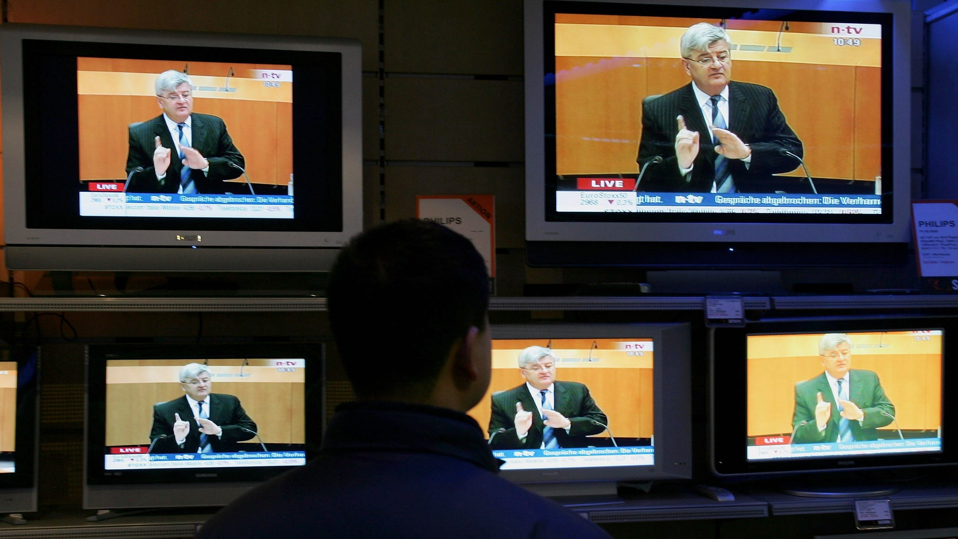 HAMBURG, GERMANY - APRIL 25:  A man watches TVs on sale in Hamburg show German Foreign Minister Joschka Fischer testifying live in front of the visa investigation committee on April 25, 2005 in Berlin, Germany. The committee, taking place in Berlin, is investigating allegations that an overly generous policy of granting visa applications at the German embassy in Kiev allowed thousands of people to enter the European Union, much to the benefit of people smugglers and other criminal gangs. (Photo by Andreas Rentz/Getty Images)