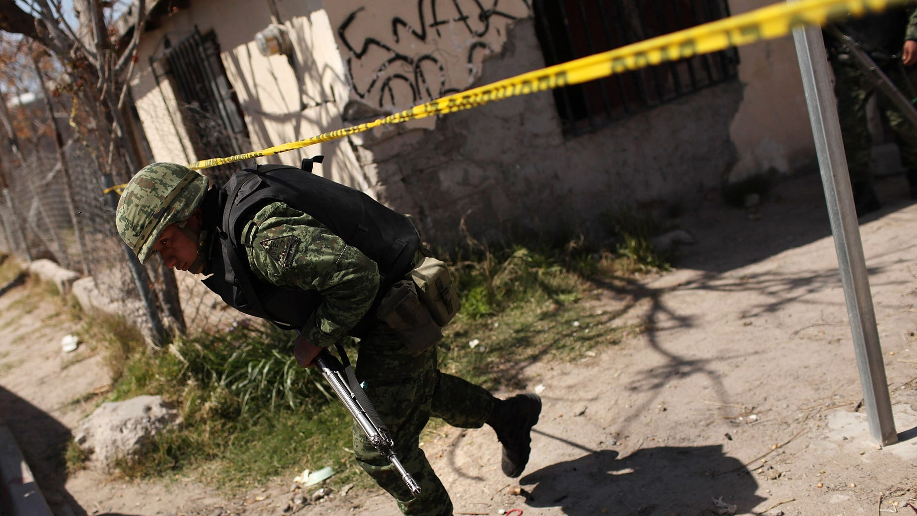 JUAREZ, MEXICO - MARCH 24:  Members of the Mexican military police keep guard at the scene of the murder of two women aged 17 and 21 March 24, 2010 in Juarez, Mexico. Secretary of State Hillary Rodham Clinton, Defense Secretary Robert Gates, and Homeland Security Secretary Janet Napolitano all visited Mexico yesterday for discussions centered on Mexico's endemic drug-related violence. The border city of Juarez, Mexico has been racked by violent drug-related crime recently and has quickly become one of the most dangerous cities in the world in which to live. As drug cartels have been fighting over ever-lucrative drug corridors along the United States border, the murder rate in Juarez has risen to 173 slayings for every 100,000 residents. President Felipe Calderon's strategy of sending 7000 troops to Juarez has not mitigated the situation. With a population of 1.3 million, 2,600 people died in drug-related violence last year and 500 so far this year, including two Americans recently who worked for the U.S. Consulate and were killed as they returned from a child's party.  (Photo by Spencer Platt/Getty Images)