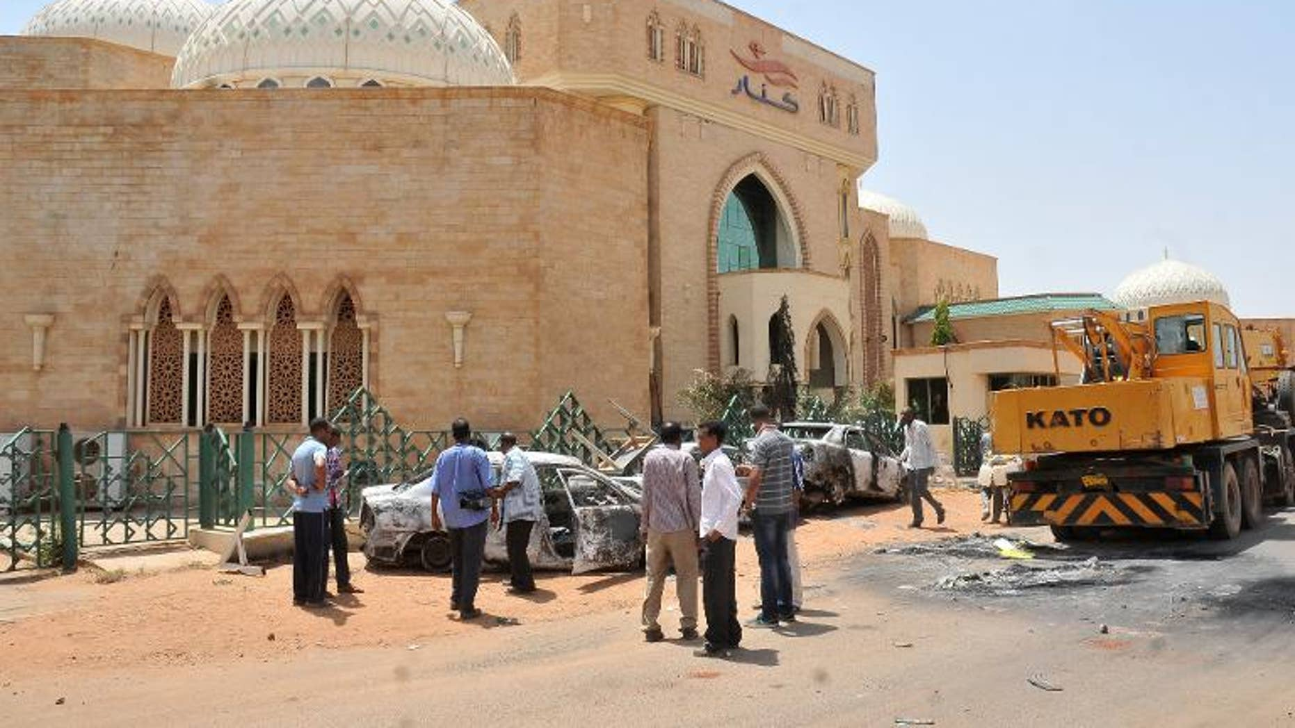 People look at burnt vehicles on September 26, 2013 in the Sudanese capital Khartoum after rioting erupted following a decision by the government to scrap fuel subsidies