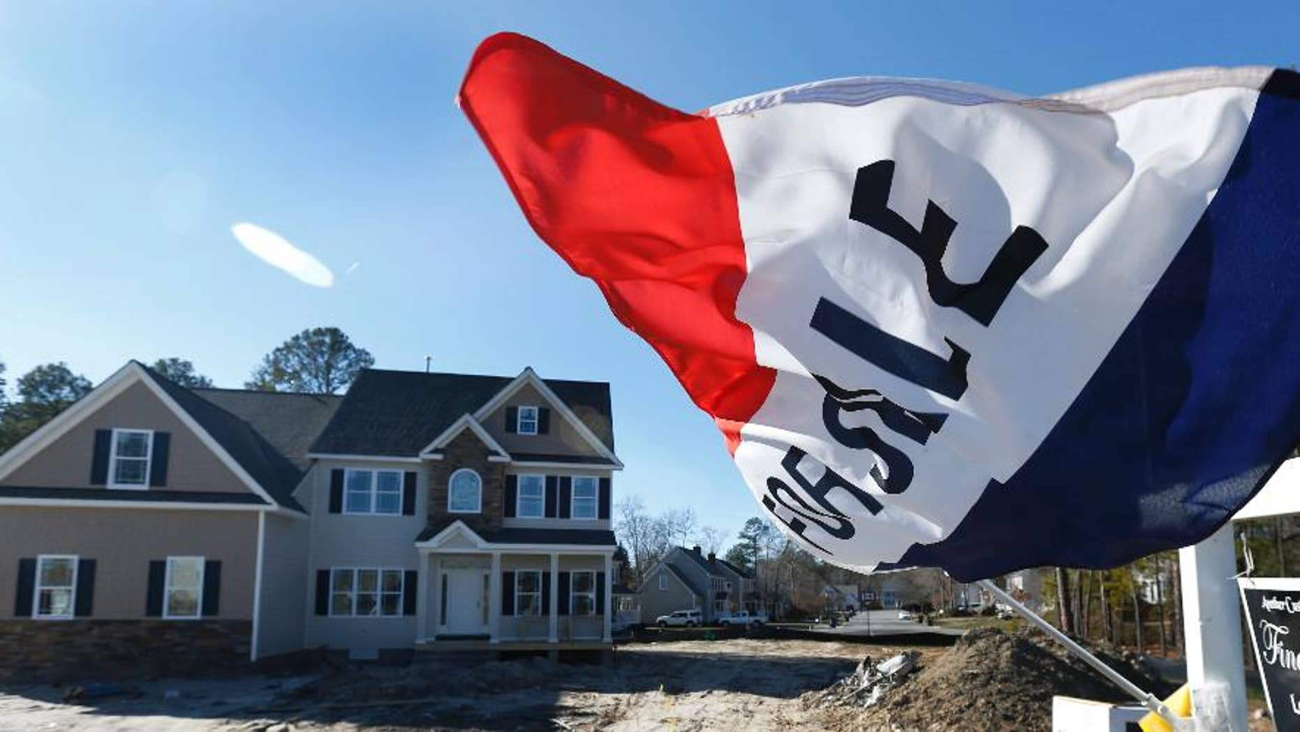 In this Thursday, Jan. 8, 2015 photo, a flag flaps in the breeze in front of a new home for sale in Richmond, Va. The Commerce Department reports on sales of new homes for December on Tuesday, Jan. 27, 2015. (AP Photo/Steve Helber)