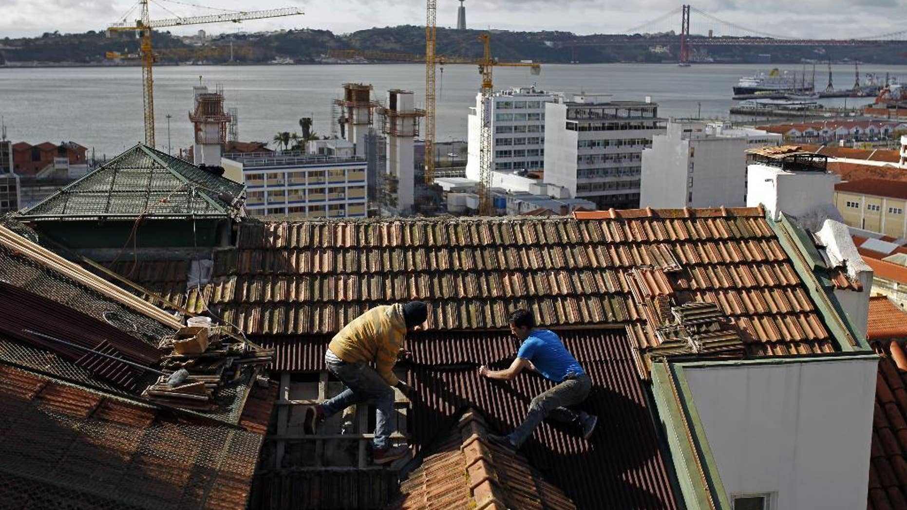 FILE - In this Feb. 28, 2014 file photo, construction workers repair the roof of a building in Lisbon. The country's construction sector collapsed amid the financial crisis, which saw the state take a 78 billion-euro ($87 billion) bailout in 2011. The number of construction workers has more than halved from 612,000 in 2005 to roughly 277,000. (AP Photo/Francisco Seco)