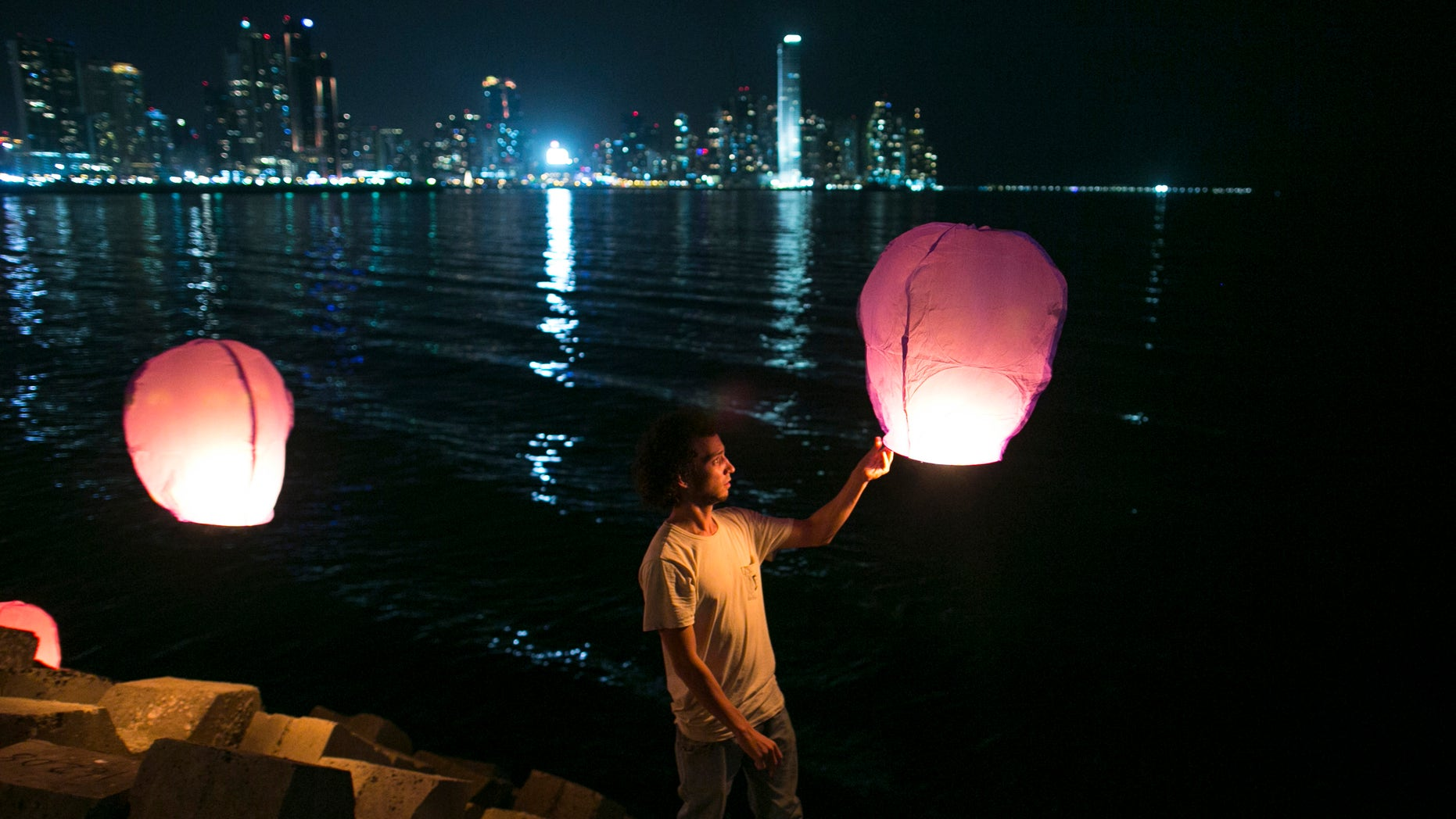 People prepare to release paper lanterns in the Panama City Bay as part of a public event held as a tribute to the victims of the US invasion of  Panama one day before the 25th anniversary of the military operation in Panama City, Friday, Dec. 19, 2014. On Dec. 20, 1989, US armed forces in an operation code-named Just Cause, invaded Panama to overthrow Panama's dictator Manuel Antonio Noriega and the Panamanian Defense Forces were dissolved.  (AP Photo/Tito Herrera)