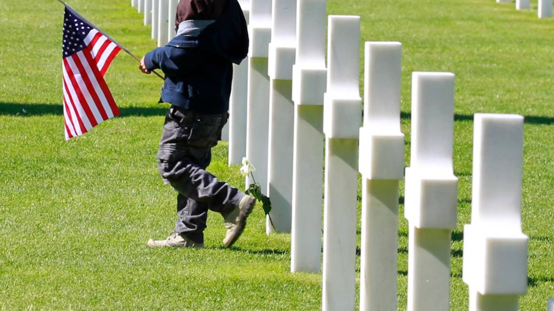 A young visitor carrying the U.S. flag walks among graves at the Colleville American military cemetery, in Colleville sur Mer, western France, Saturday June 6, 2015,  on  the 71th anniversary of the D-Day landing.  D-Day marked the start of a Europe invasion, as many thousands of Allied troops began landing on the beaches of Normandy in northern France in 1944 at the start of a major offensive against the Nazi German forces, an offensive which cost the lives of many thousands. (AP Photo/Remy de la Mauviniere)
