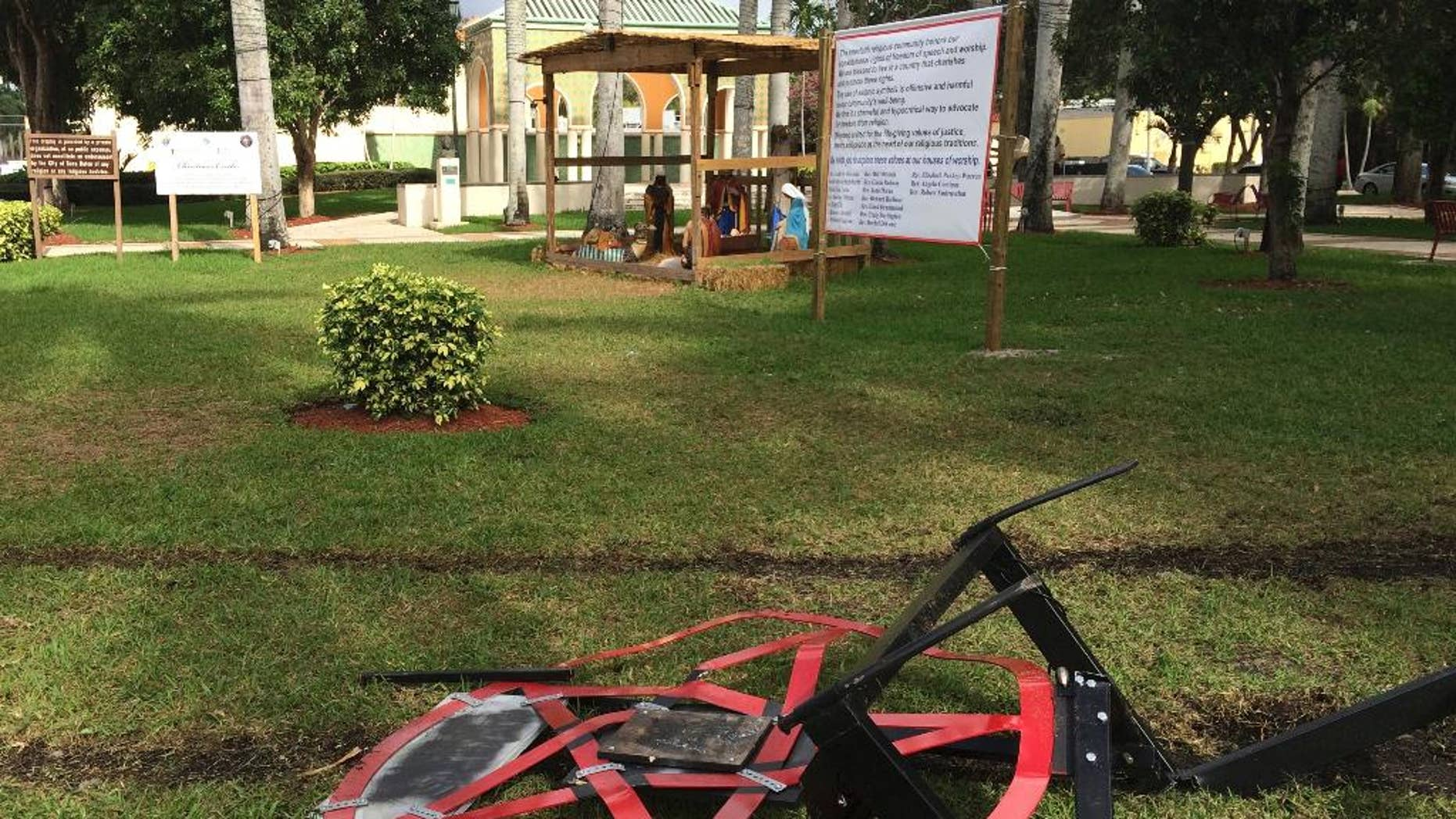 A satanic pentagram erected by atheist Preston Smith lies damaged in Boca Raton's Sanborn Square, Fla. on Tuesday, Dec. 20, 2016. Smith erected the pentagram earlier this month to protest a Nativity scene place in the city-owned square. Vandals apparently dragged down the 300-pound statue using a chain attached to a vehicle. (AP Photo/Terry Spencer)