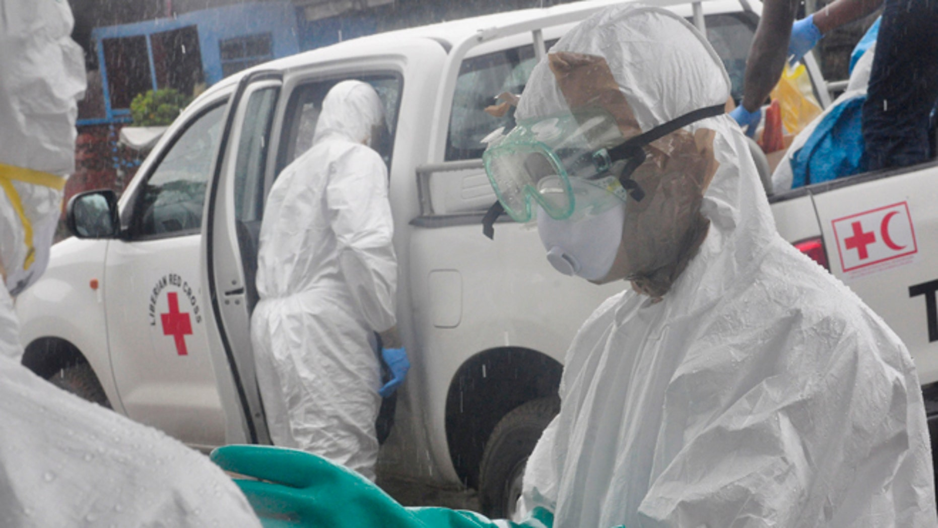 Health workers dressed in protective gear prepare to load the body of a woman suspected to have died from Ebola virus, in New Kru Town at the outskirt of  Monrovia, Liberia, Wednesday, Oct. 8, 2014. Liberia has been among the hardest hit nations at the centre of the long outbreak, which has killed more than 3,000 people, as of Friday, there had been 3,834 confirmed Ebola cases and 2,069 deaths in Liberia, according to the World Health Organization. Forty-four percent of the Ebola cases were reported in the past three weeks, a signal that the infectious disease is spreading.(AP Photo/Abbas Dulleh)