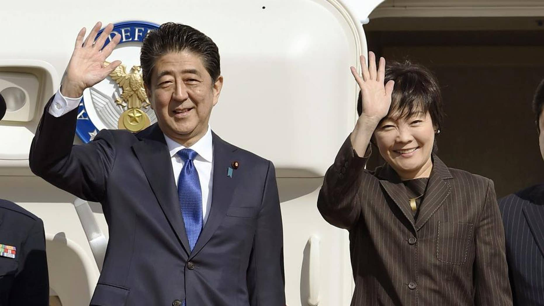 Nov. 17, 2016: Japanese Prime Minister Shinzo Abe and his wife Akie wave prior to their departure to New York, at Haneda airport in Tokyo.