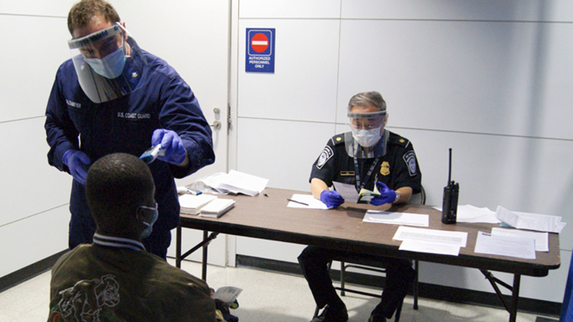 FILE- In this Thursday, Oct. 16, 2014, file photo released by U.S. Customs and Border Protection, U.S. Coast Guard Health Technician Nathan Wallenmeyer, left, and CBP supervisor Sam Ko, right, conduct prescreening measures on a passenger who has arrived from Sierra Leone at O'Hare International Airport's Terminal 5 in Chicago. Demands are rising in Washington for the U.S. to ban travelers from countries in West Africa, but the Obama administration is resisting and says the screening measures already in place for travelers are more effective. (AP Photo/U.S. Customs and Border Protection, Melissa Maraj, File)