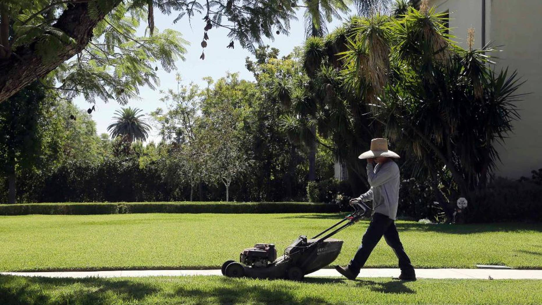 File - In this Oct. 1, 2015 file photo, a gardener mows a lawn in Pasadena, Calif. State officials say residents of drought-weary California in November missed their 25 percent water conservation mandate for a second month running. The chair of the State Water Resources Control Board, says California remains on course to beat its long-term goal through February. (AP Photo/Nick Ut, File)