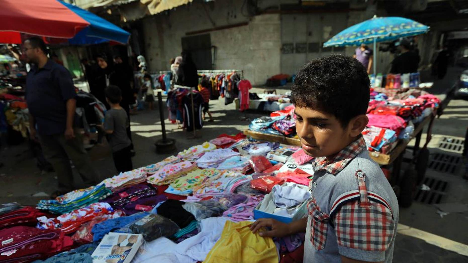 A Palestinian vendor arranges his merchandise at a market in Gaza City, northern Gaza Strip, Wednesday, Aug. 6, 2014. A cease-fire between Israel and Hamas that ended a month of fighting is holding for a second day, ahead of negotiations in Cairo on a long-term truce and a broader deal for the war-ravaged Gaza Strip. (AP Photo/Lefteris Pitarakis)