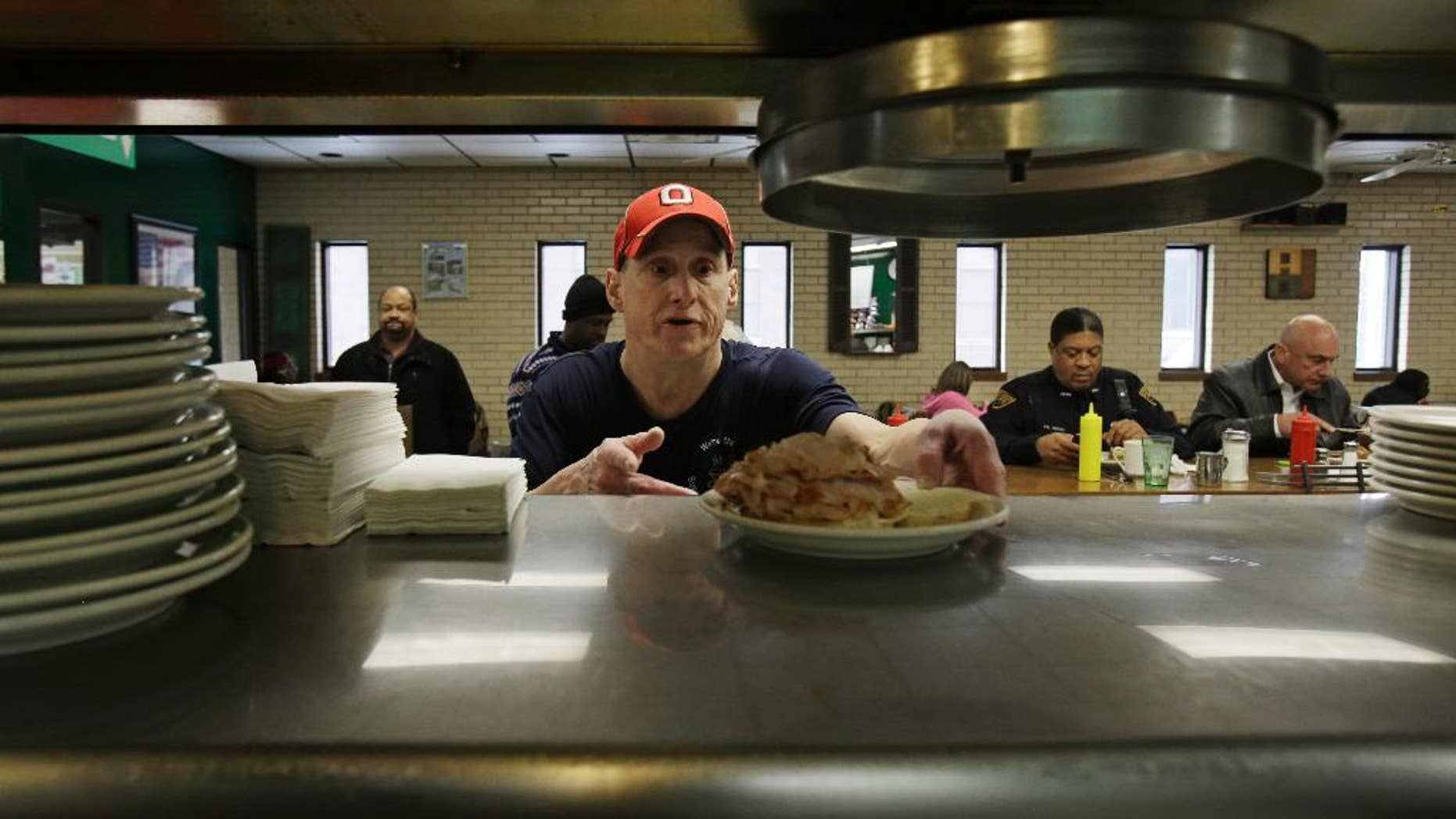 In this Jan. 23, 2015 photo, Mark Childers grabs a turkey reuben sandwich to deliver to a customer at the Superior Restaurant Friday, in Cleveland. The Labor Department reports on state unemployment rates for January on Tuesday, March 17, 2015. (AP Photo/Tony Dejak)