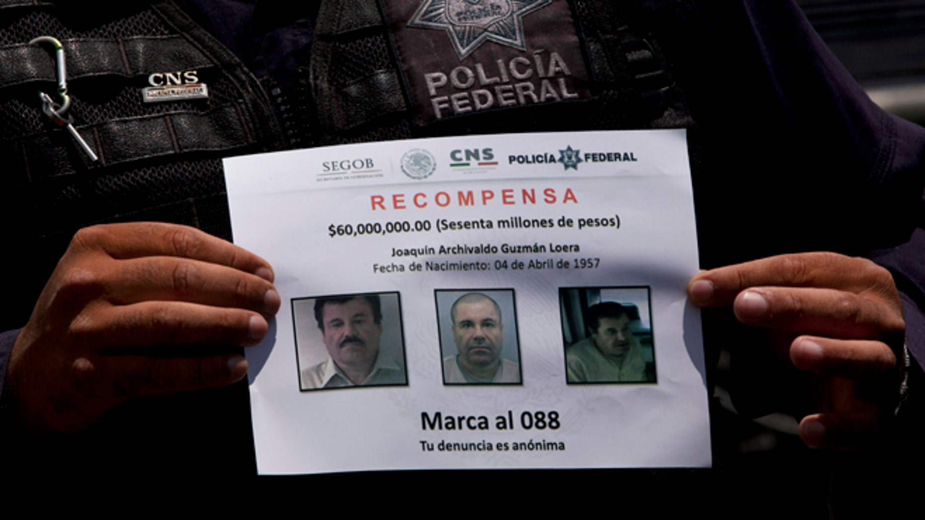 """In this July 16, 2015, photo, a Federal Police shows a reward notice for information leading to the capture of drug lord Joaquin """"El Chapo"""" Guzman, who made his escape from the Altiplano maximum security prison via an underground tunnel,  in Almoloya, west of Mexico City. The Drug Enforcement Administration's deputy administrator says he is confident one of the world's most-wanted drug traffickers will be captured again after a brazen weekend escape from a maximum-security Mexican prison.  (AP Photo/Marco Ugarte)"""