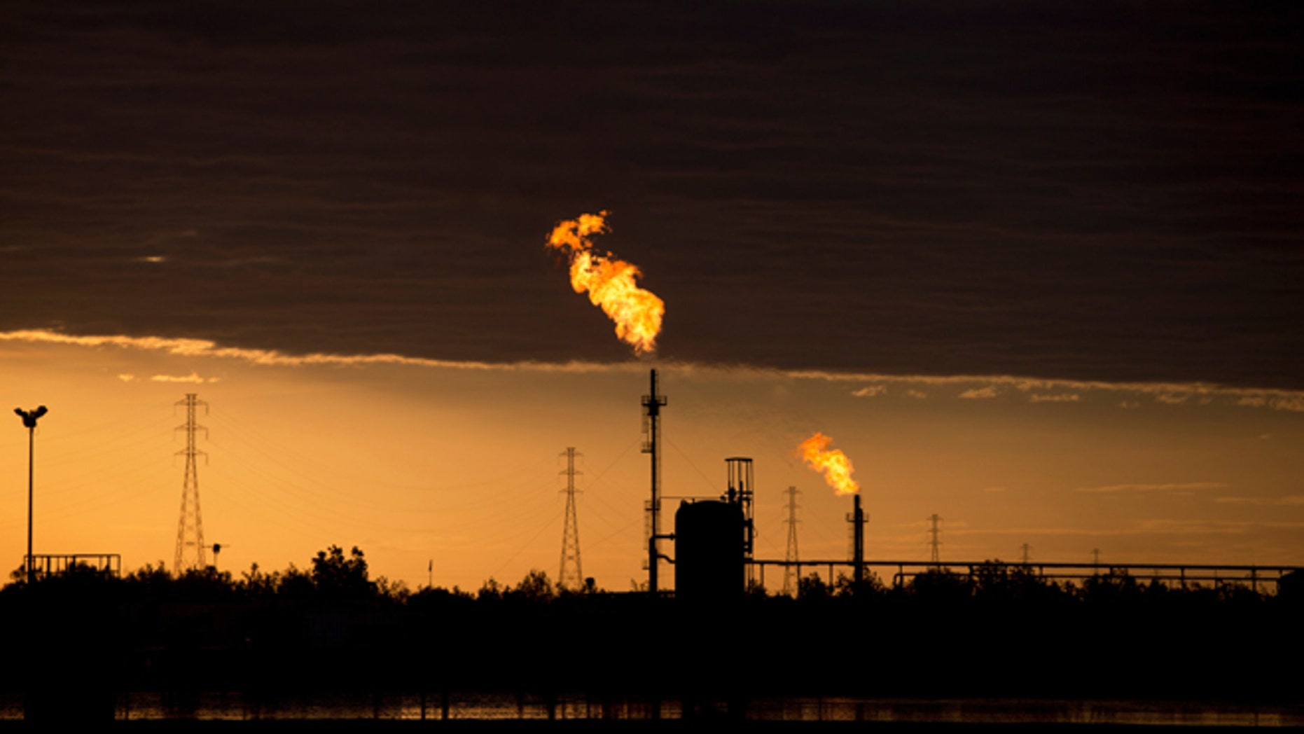 In this Feb. 18, 2015 photo, flames burn at an oil complex near El Tigre, a town located within Venezuela's Hugo Chavez oil belt, formally known as the Orinoco Belt. The Costa Rica-sized area is home to the worlds largest oil reserves and about half of Venezuelas current production. (AP Photo/Fernando Llano)